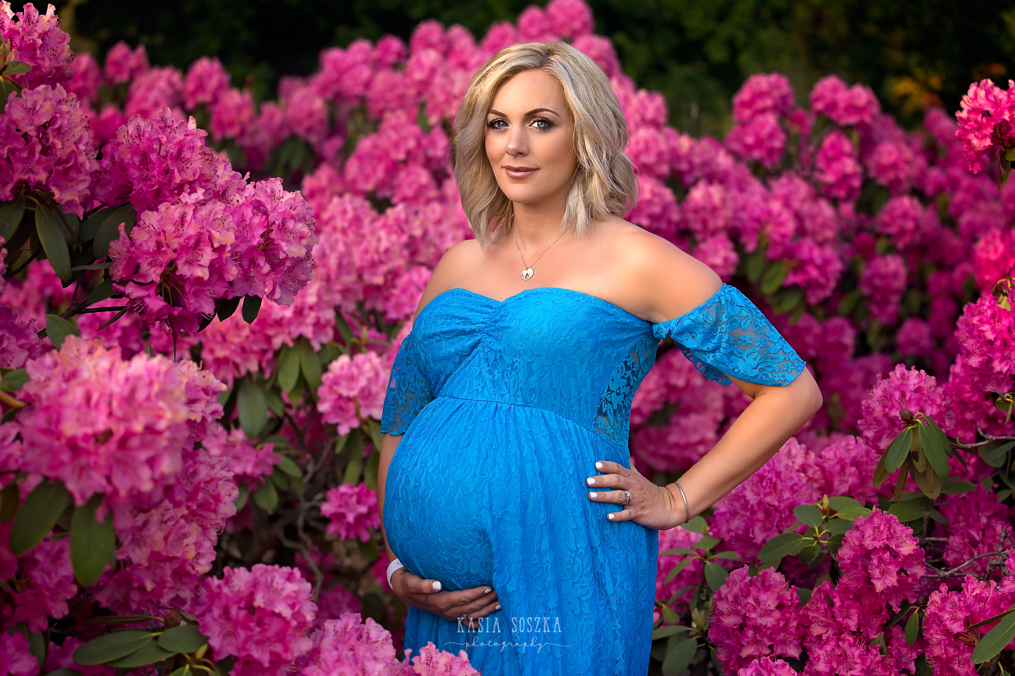 Maternity photography Yorkshire: beautiful blond expecting mother in a long blue dress standing by a pink rhododendron bush.