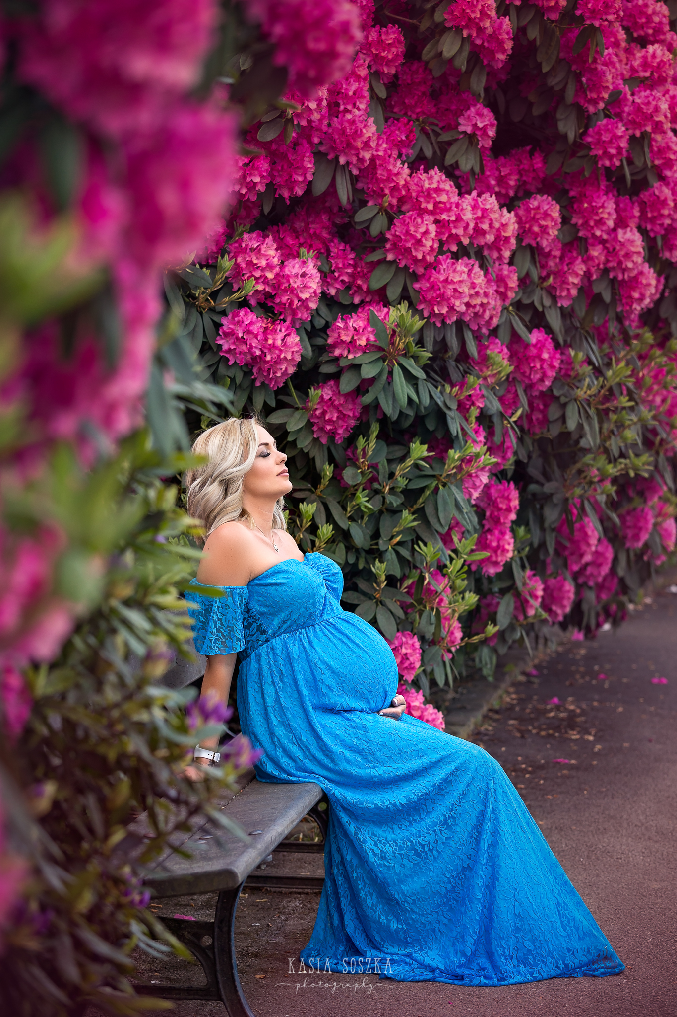 Leeds maternity photography: stunning blond mum-to-be in a long blue dress resting on a bench in a beautiful spring garden.