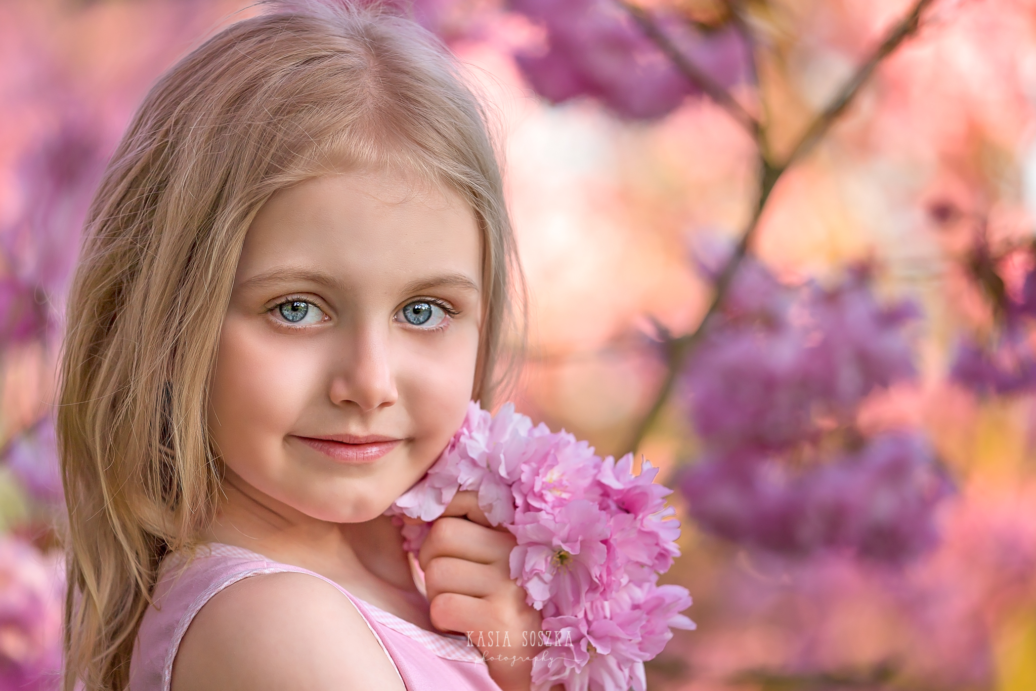 Leeds child photography Bradford child session York children photography: pretty little blond girl in a pink dress holding pink cherry blossoms