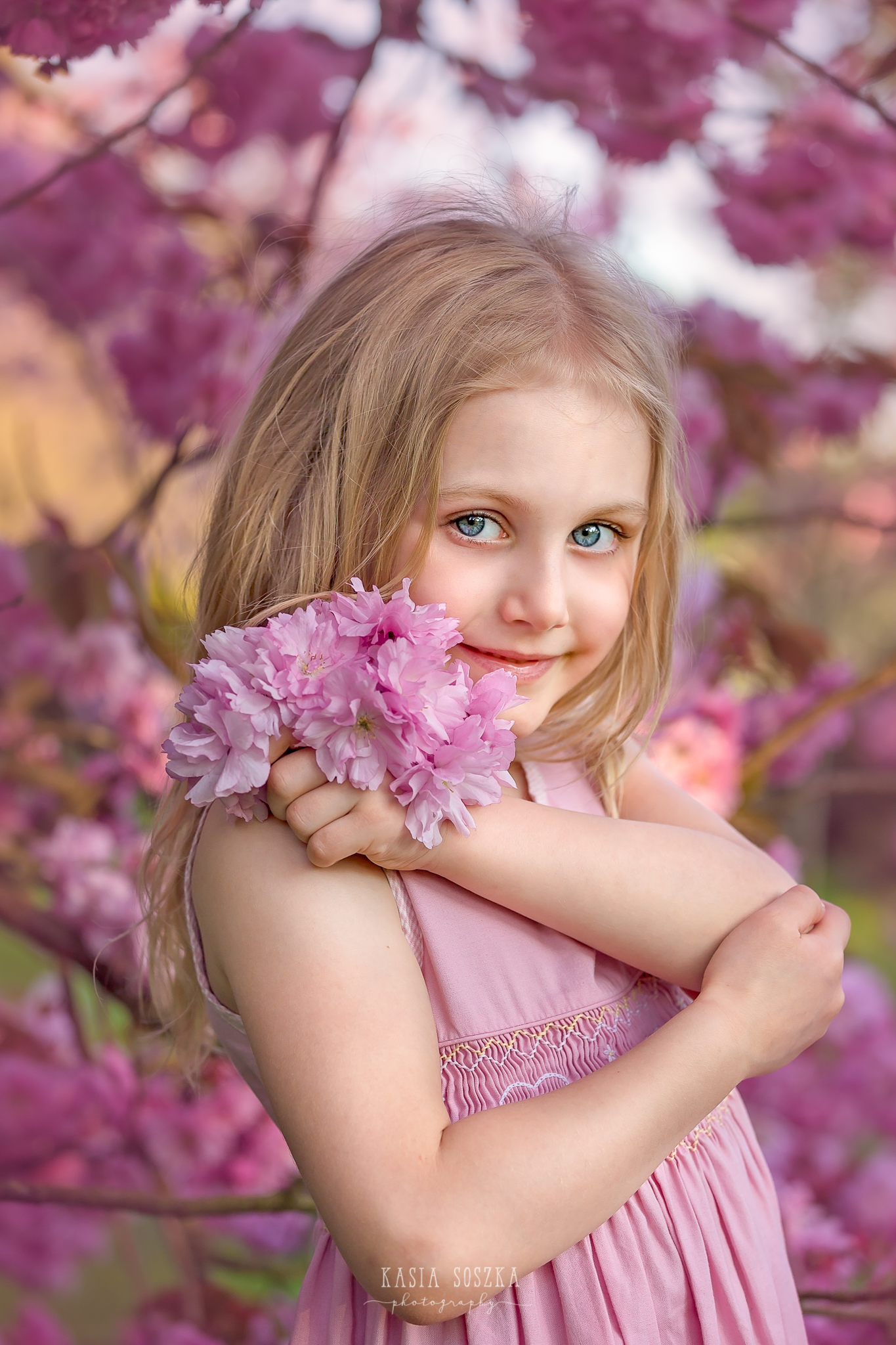 Leeds child photography Bradford child session York children photography: pretty little blond girl in a pink dress under blooming cherry tree