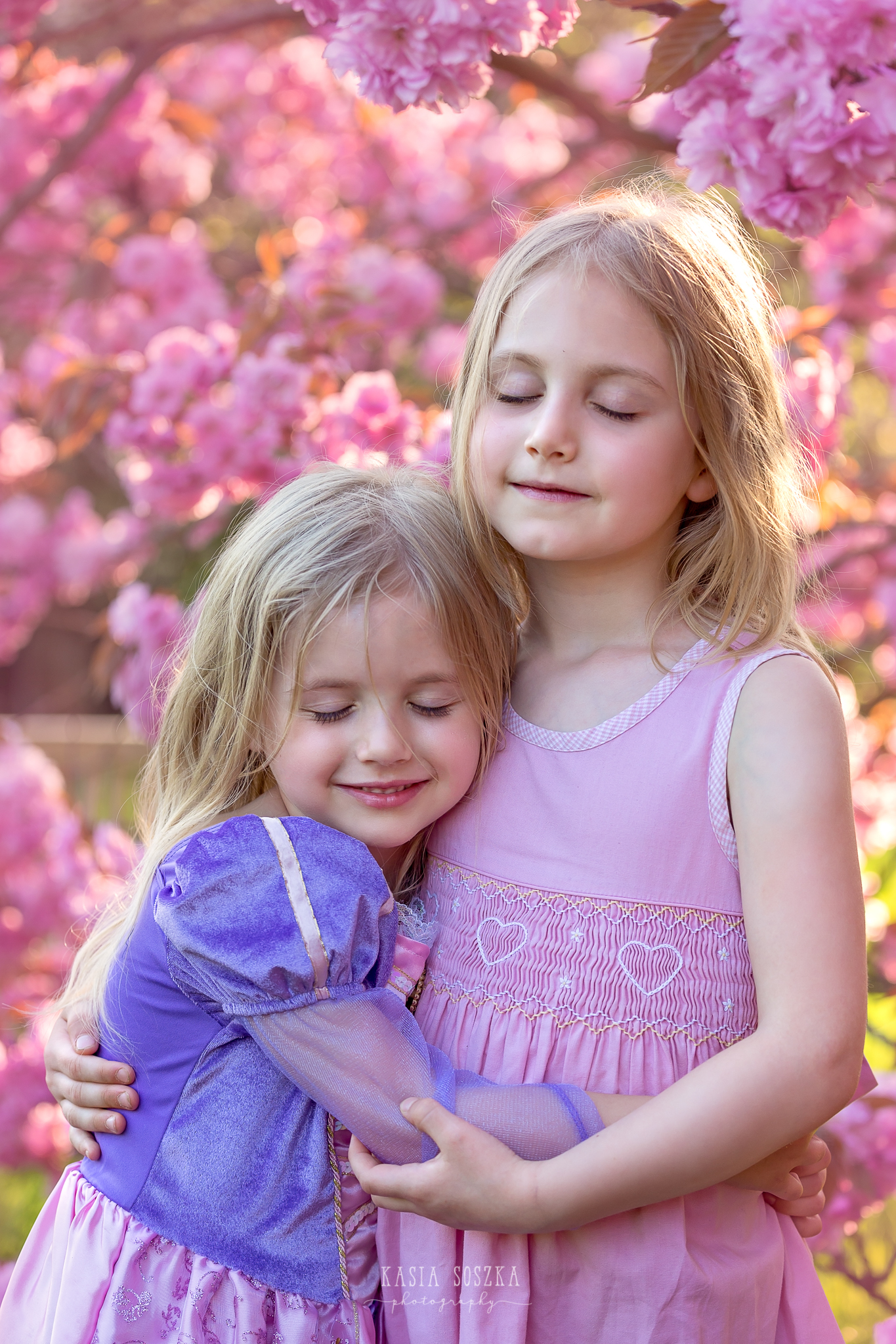 Leeds child photography Bradford children session York children photography: pretty blond sisters hugging each under under a blooming cherry tree
