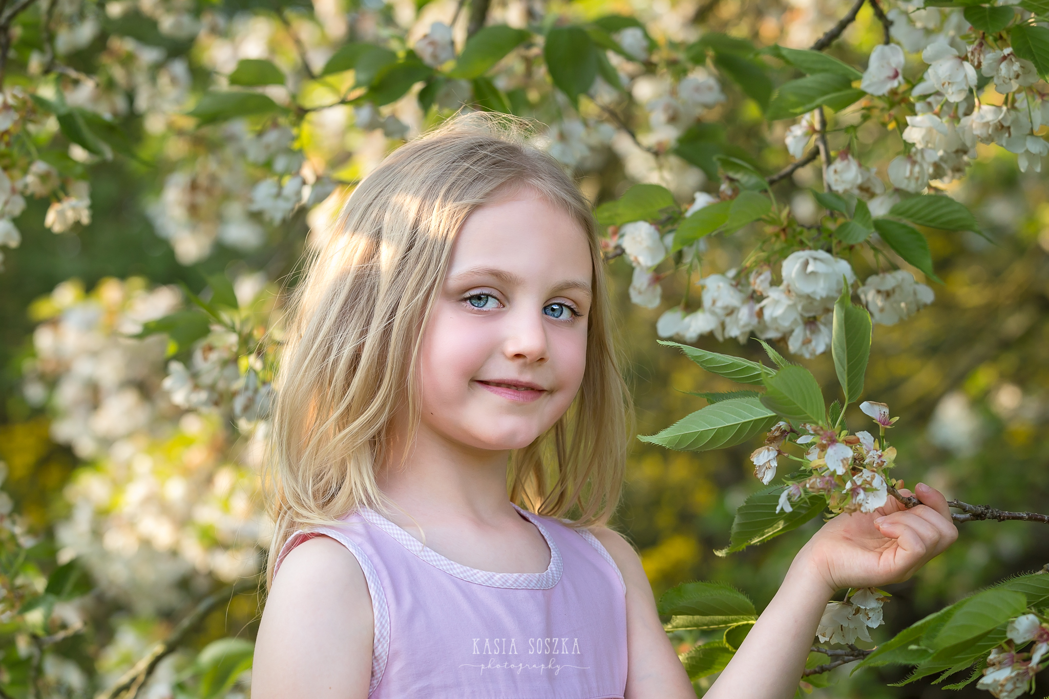 Leeds child photography Bradford child session York children photography: pretty little blond girl in a pink dress holding a branch of a blossoming apple tree