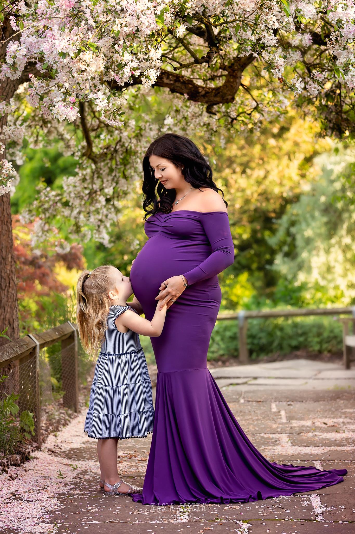 Leeds maternity photography Leeds Bradford York Harrogate maternity photographer:little girl kissing her pregnant mummy's belly in a beautiful park