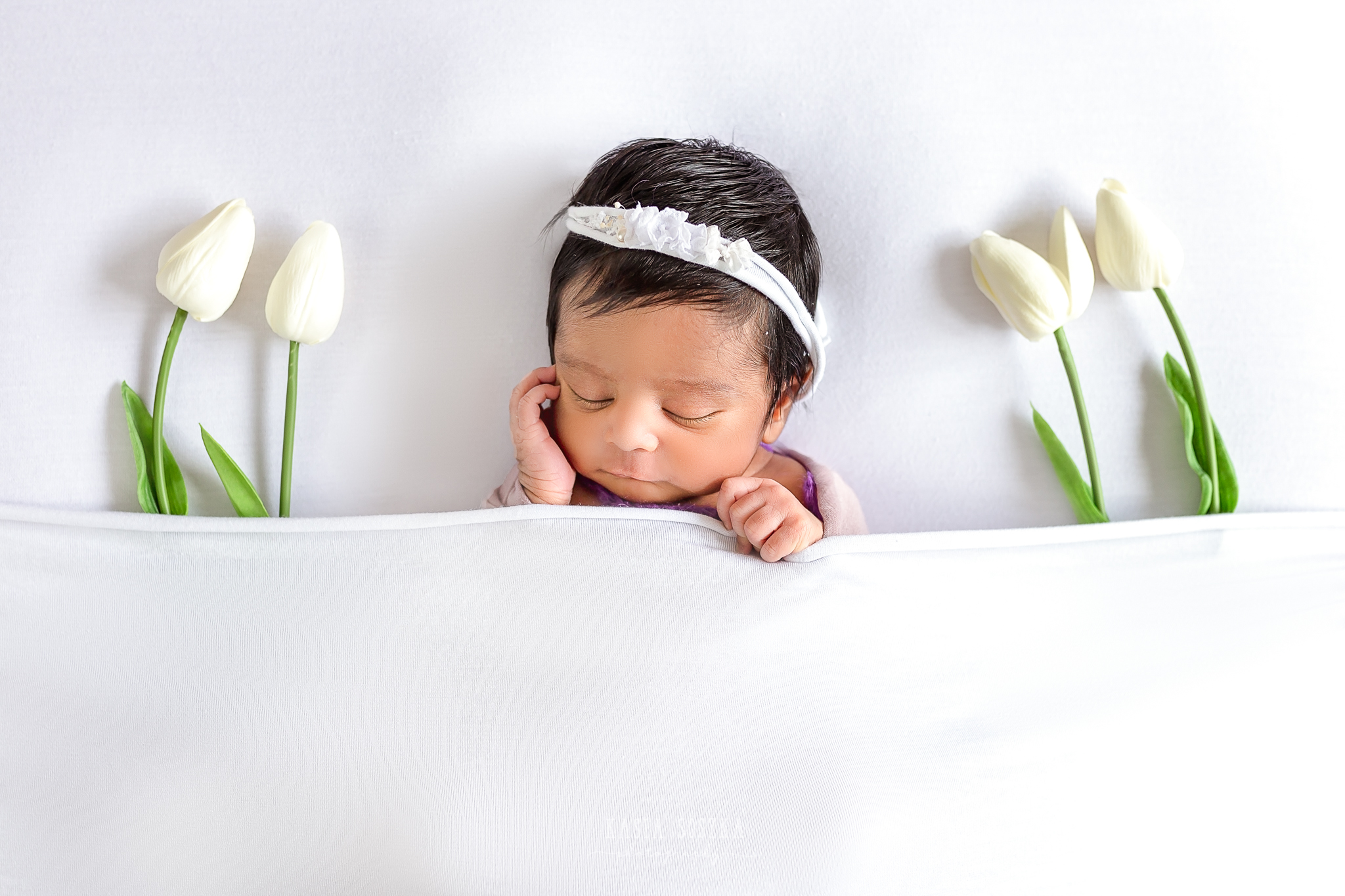 Newborn photography Leeds-Bradford-York-Harrogate: newborn baby girl sleeping in a white bed