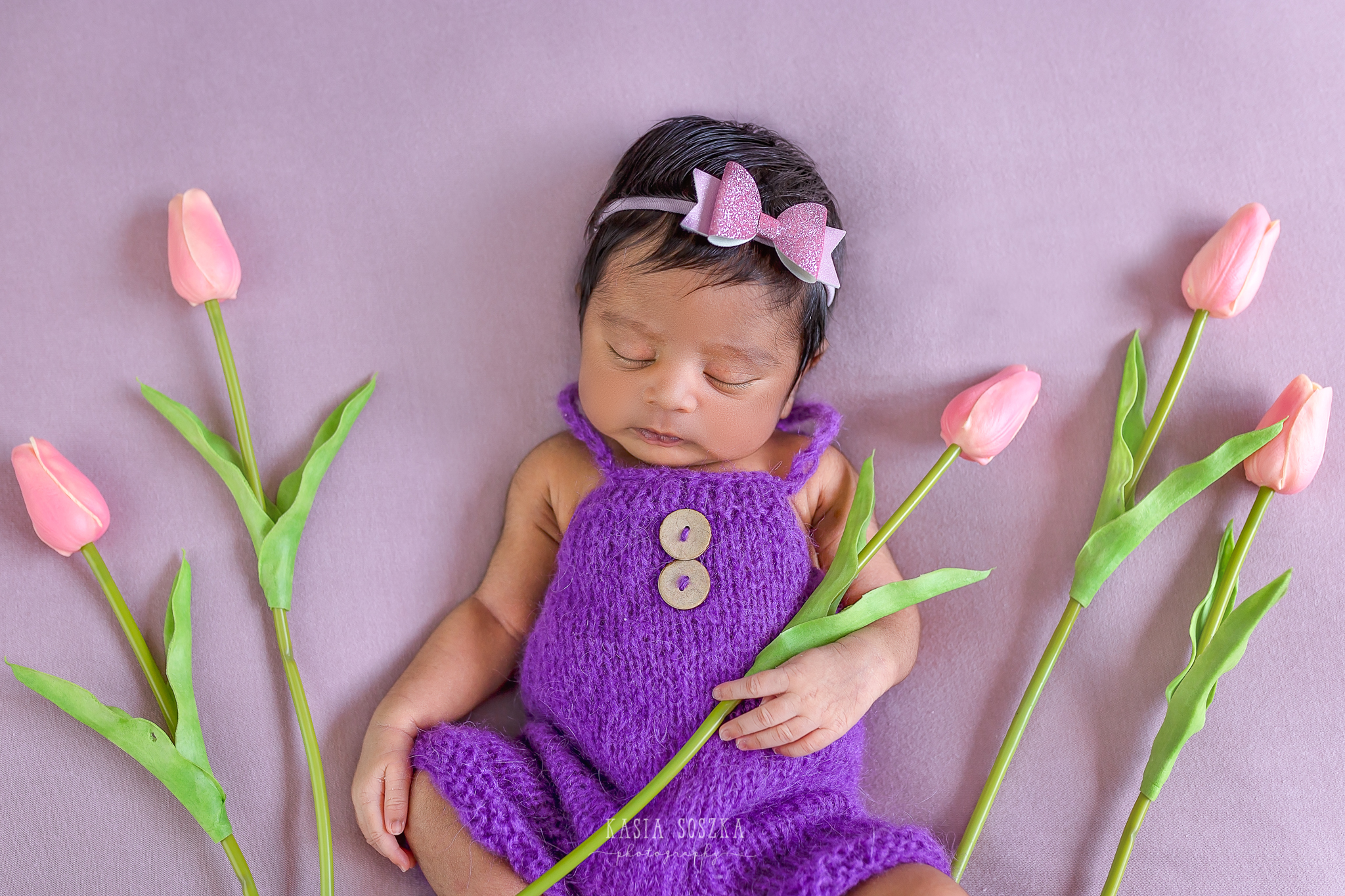 Newborn photography Leeds-Bradford-York-Harrogate: newborn baby girl wearing purple outfit on a pink blankets surrounded by pink tulips