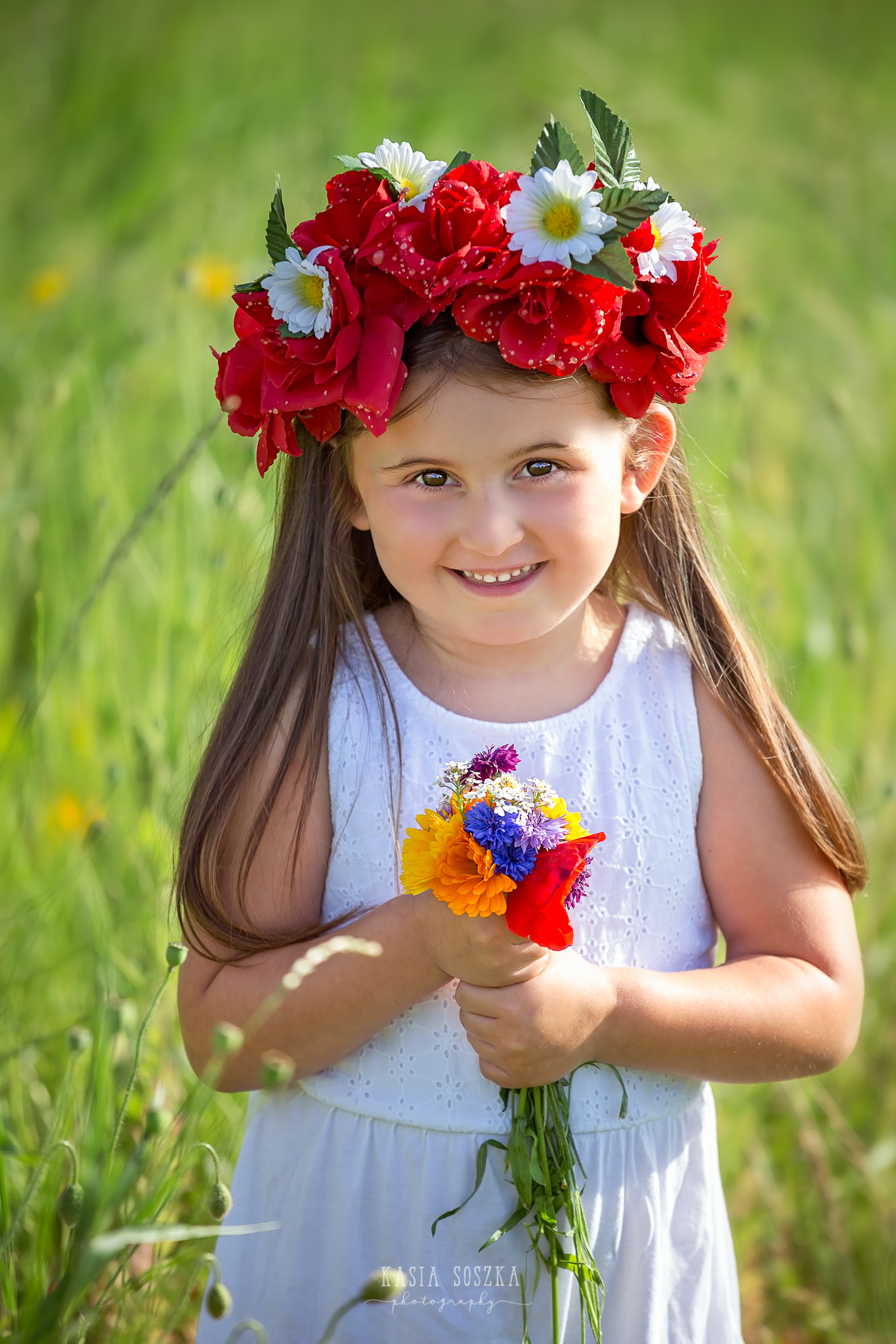 Children photography Leeds, child outdoor summer session Yorkshire: happy little girl standing in the middle of a summer meadow and holding a bunch of wildflowers.