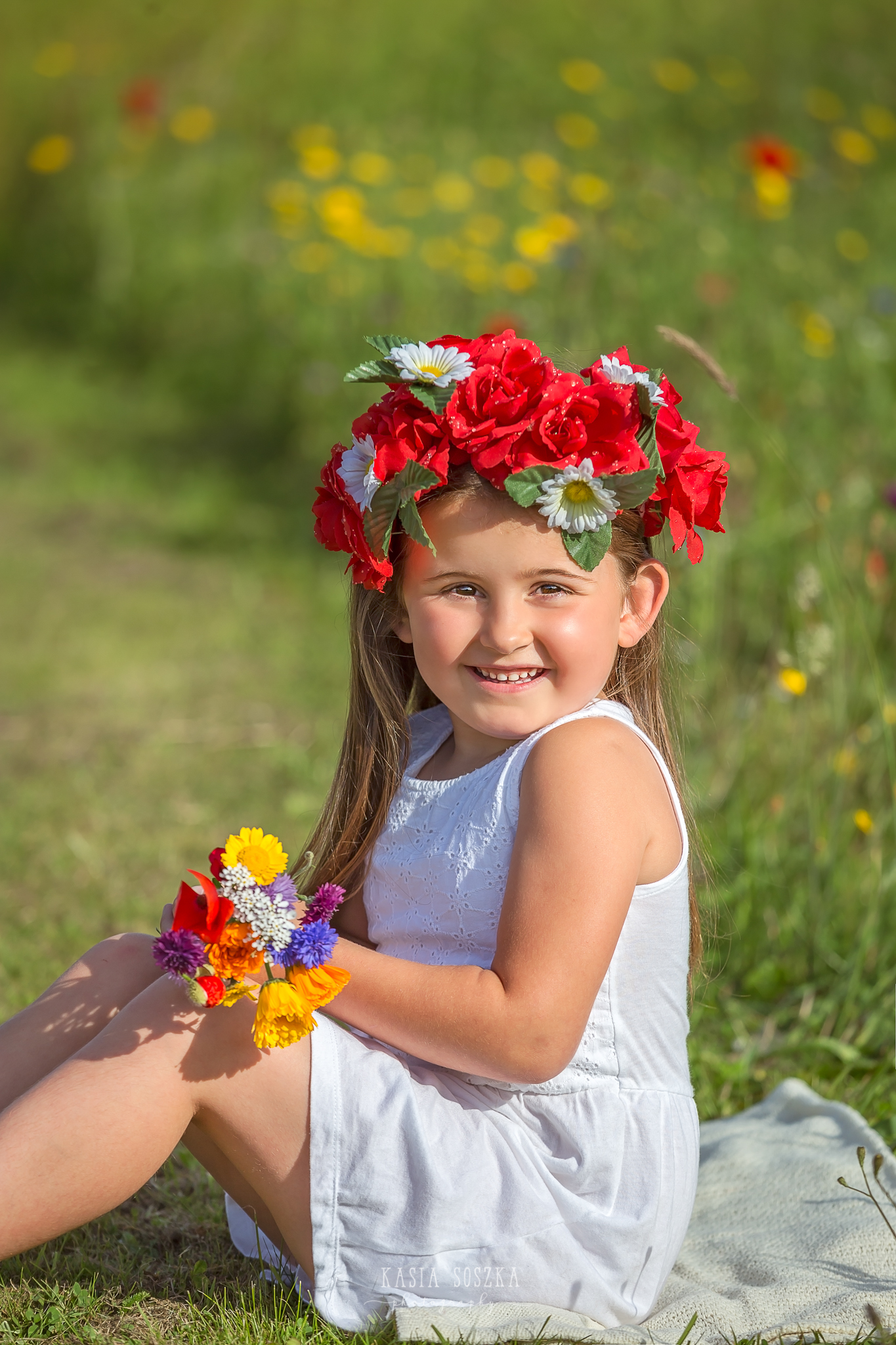 Children photography Leeds, child outdoor summer session Yorkshire: happy little girl sitting in a meadow and holding a bunch of wildflowers.