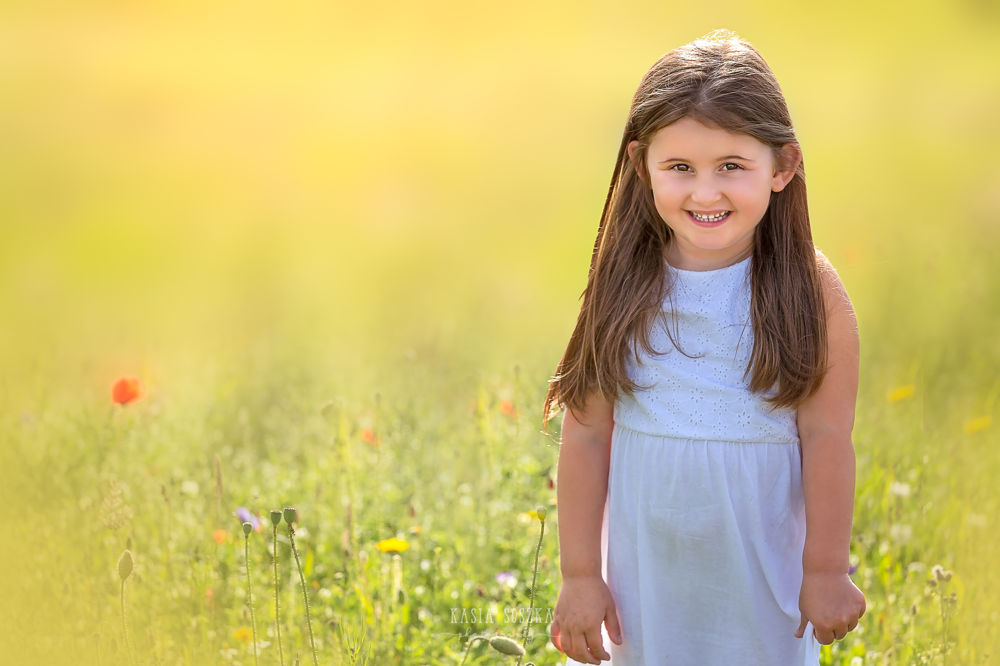 Children photography Leeds, child outdoor summer session Yorkshire: happy little girl standing in a meadow and holding a bunch of wildflowers.