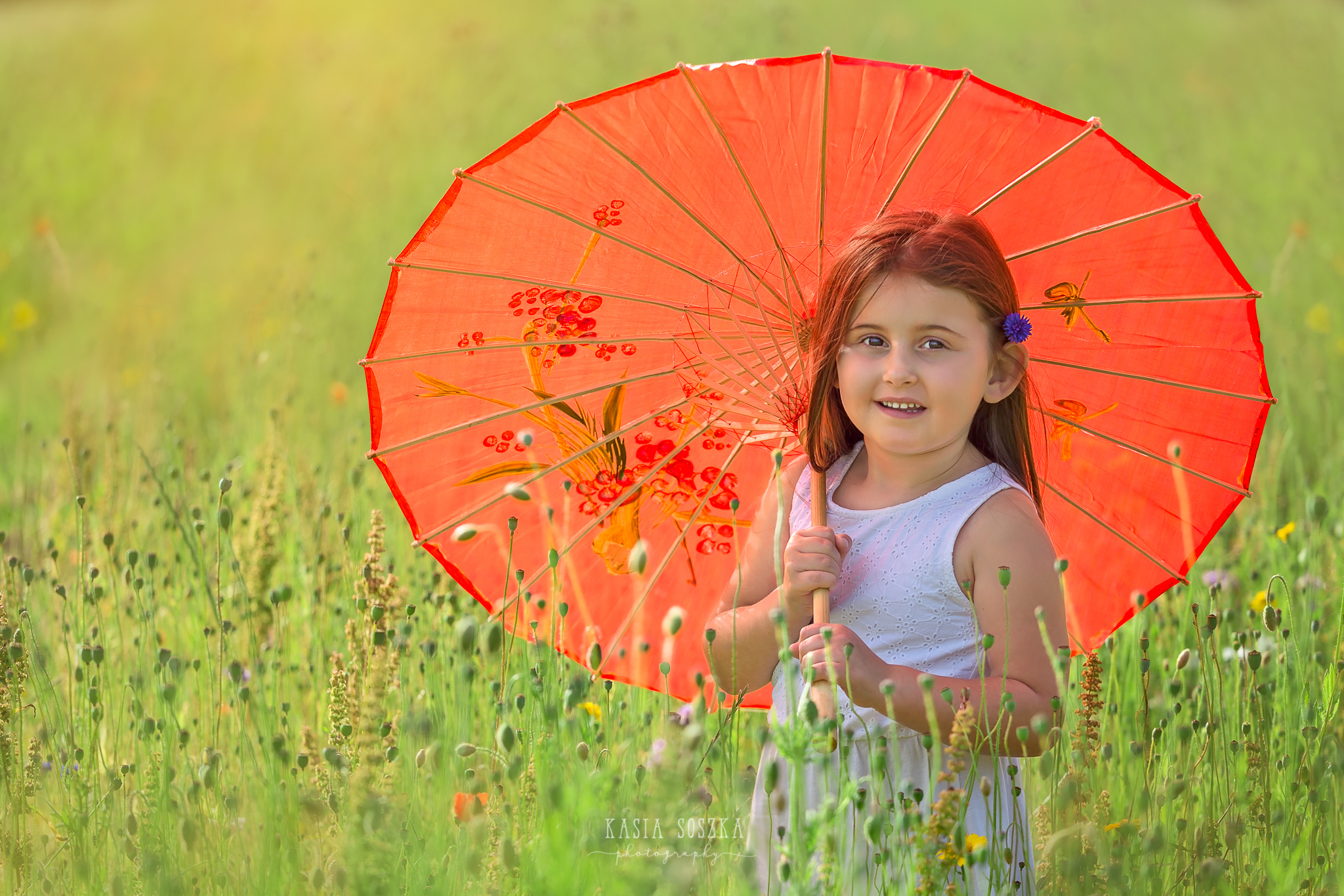Children photography Leeds, child outdoor summer session Yorkshire: happy little girl holding red umbrella in the middle of meadow