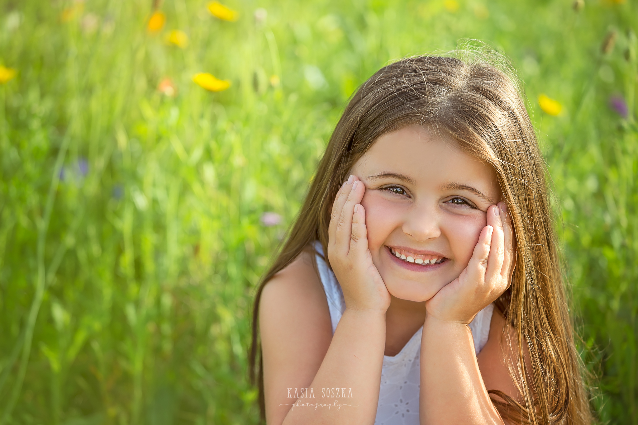 Children photography Leeds, child outdoor summer session Yorkshire: happy little girl sitting in a summer meadow