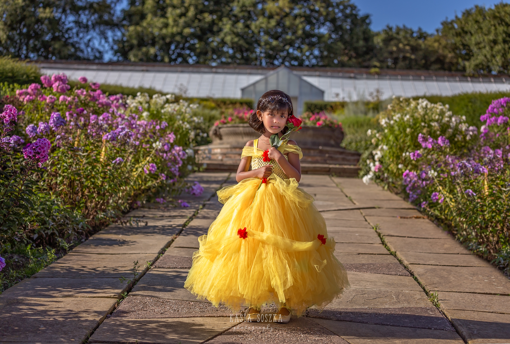 Child photography Leeds, child outdoor princess session Leeds, Yorkshire: beautiful little girl in a yellow princess dress posing for a photo in a garden