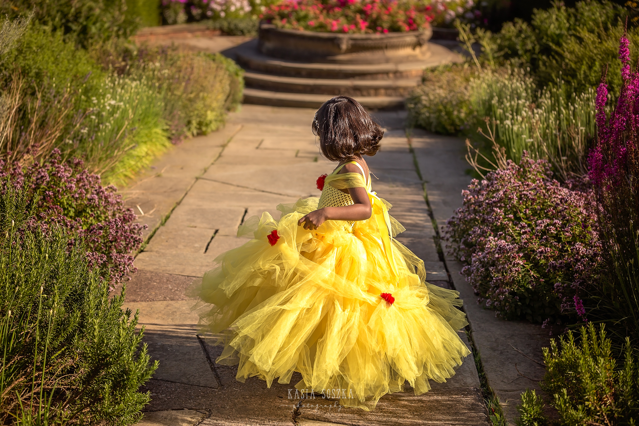 Child photography Leeds, child outdoor princess session Leeds, Yorkshire: beautiful little girl in a yellow princess dress dancing in a garden