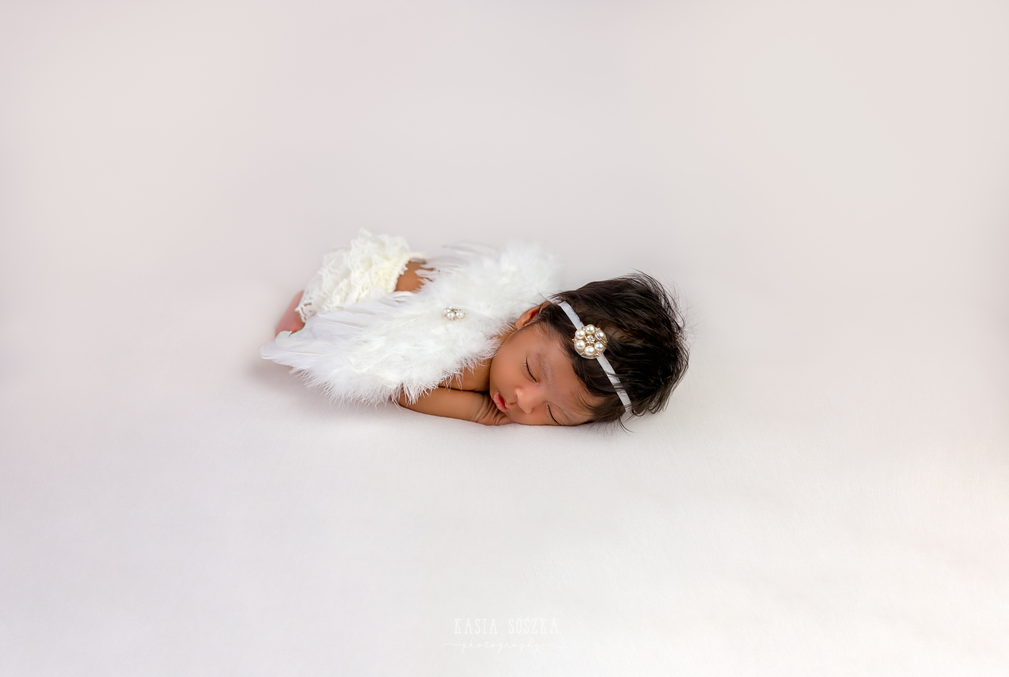 Newborn photography Leeds, Yorkshire, newborn session Leeds, York, Harrogate, Bradford: newborn baby girl with angel wings sleeping on a white blanket