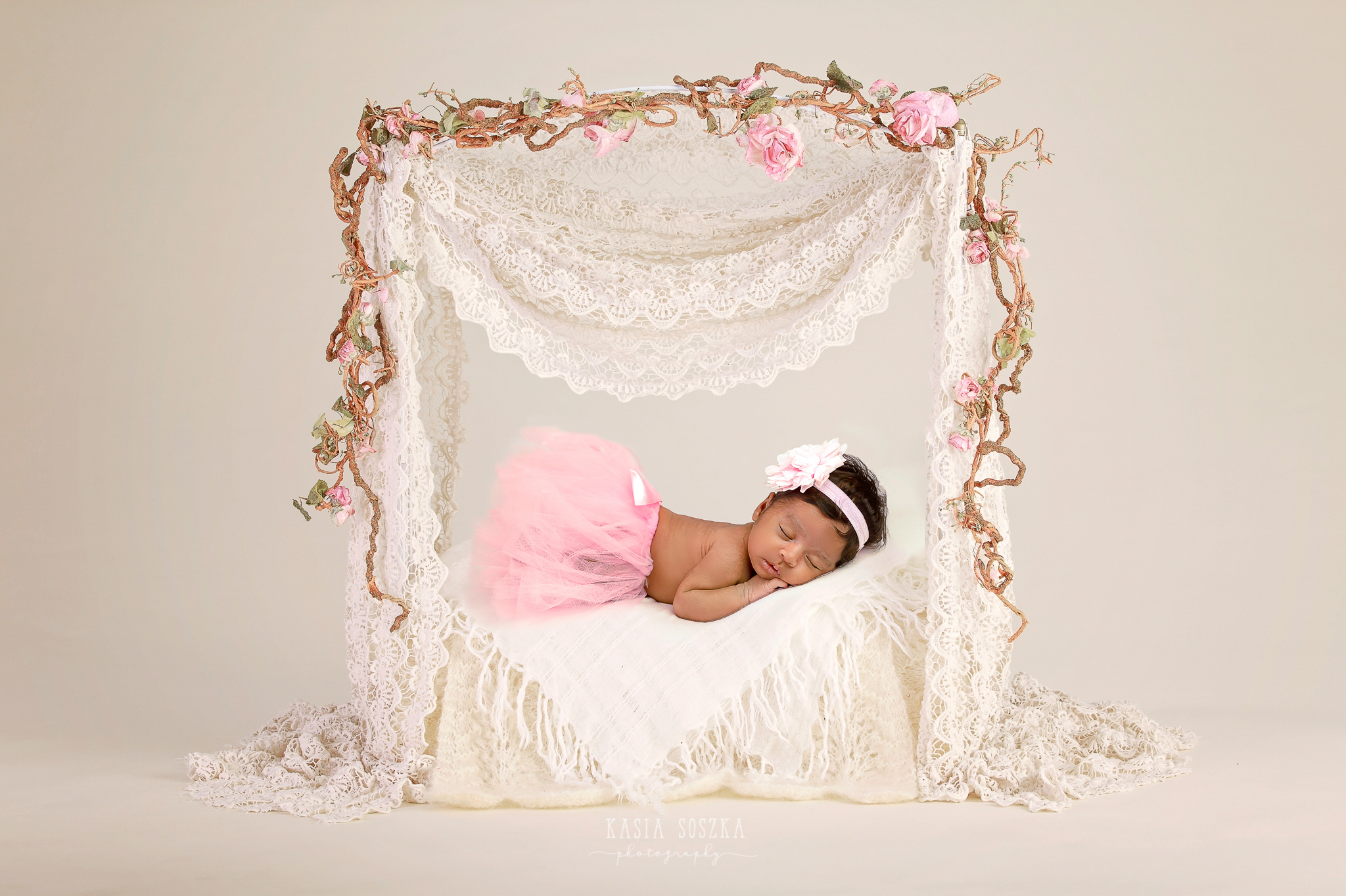 Newborn photography Leeds, Yorkshire, newborn session Leeds, York, Harrogate, Bradford: newborn baby girl in a pink tutu skirt sleeping in a cute poster bed