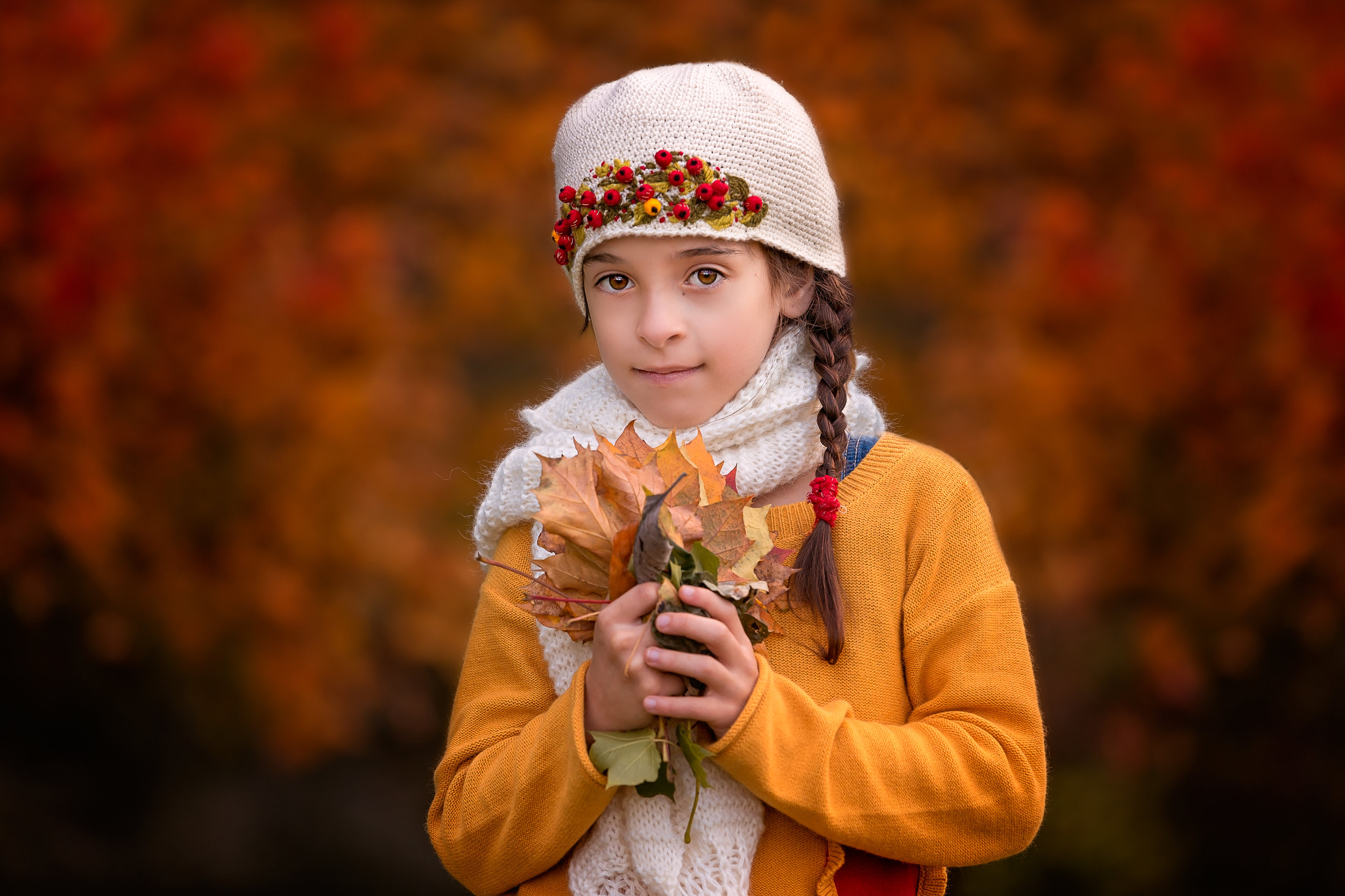 Child photography Leeds, York, Bradford, Harrogate: girl in a yellow sweater holding autumn leaves. Child autumn session in Leeds, Yorkshire