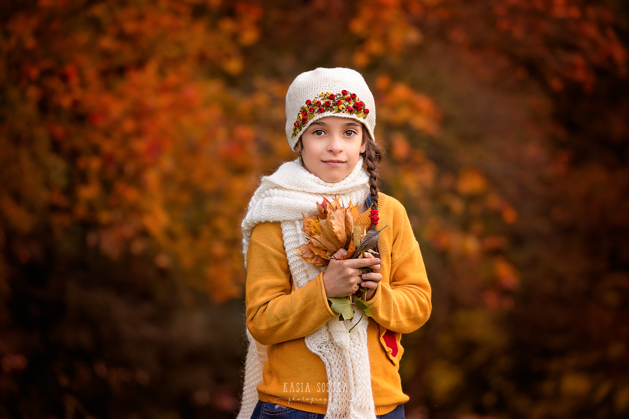 Children photography Leeds, York, Bradford, Harrogate: girl in a yellow sweater holding autumn leaves. Child autumn session in Leeds, Yorkshire