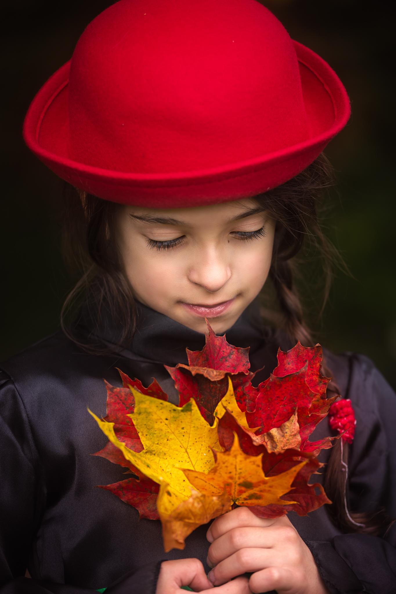 Children photography Leeds, York, Bradford, Harrogate: little girl in a red hat holding autumn leaves. Child autumn session in Leeds, Yorkshire