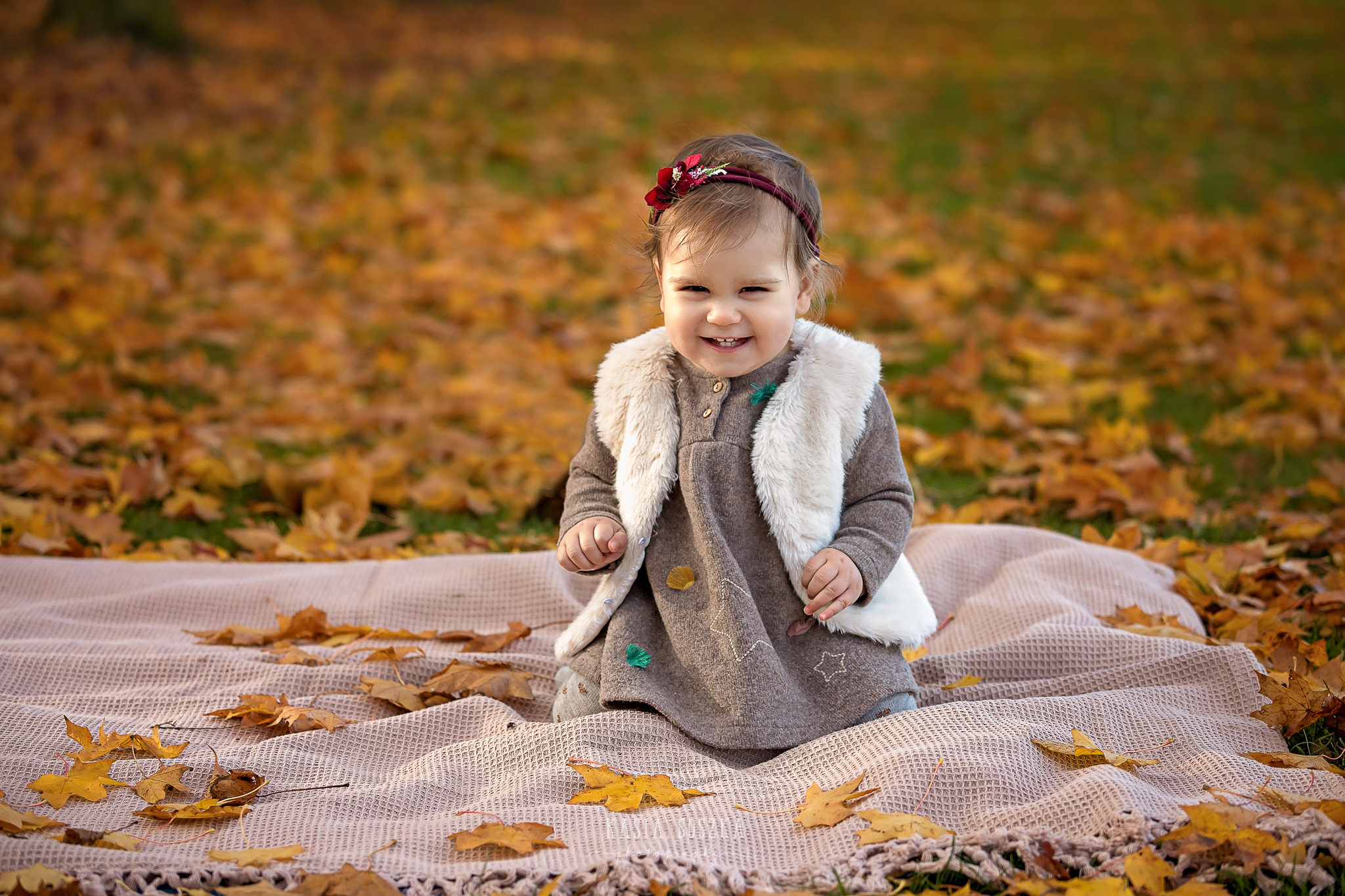 Baby milestone photography Leeds, York, Bradford, Harrogate: cute baby girl's first birthday portrait session. Autumn outdoor baby photo shoot in a park in Leeds, Yorkshire