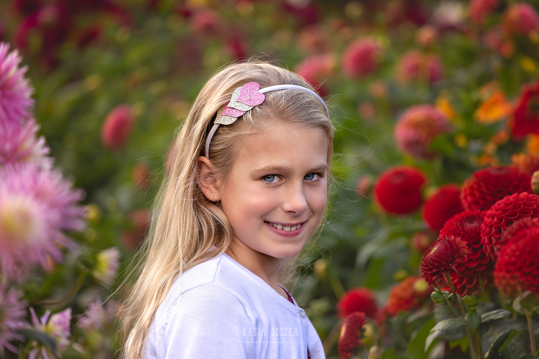 Children photography, child photographer Leeds, York, Bradford, Harrogate: pretty blond girl with blue eyes posing for a portrait against red autumn flowers