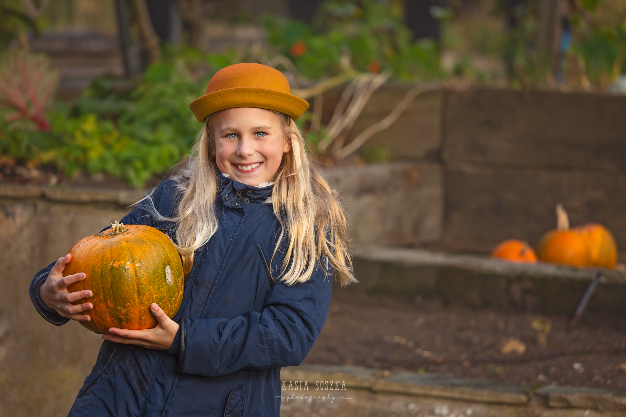 Children photography, child photographer Leeds, York, Bradford, Harrogate: pretty blond girl in a yellow hat holding a pumpkin