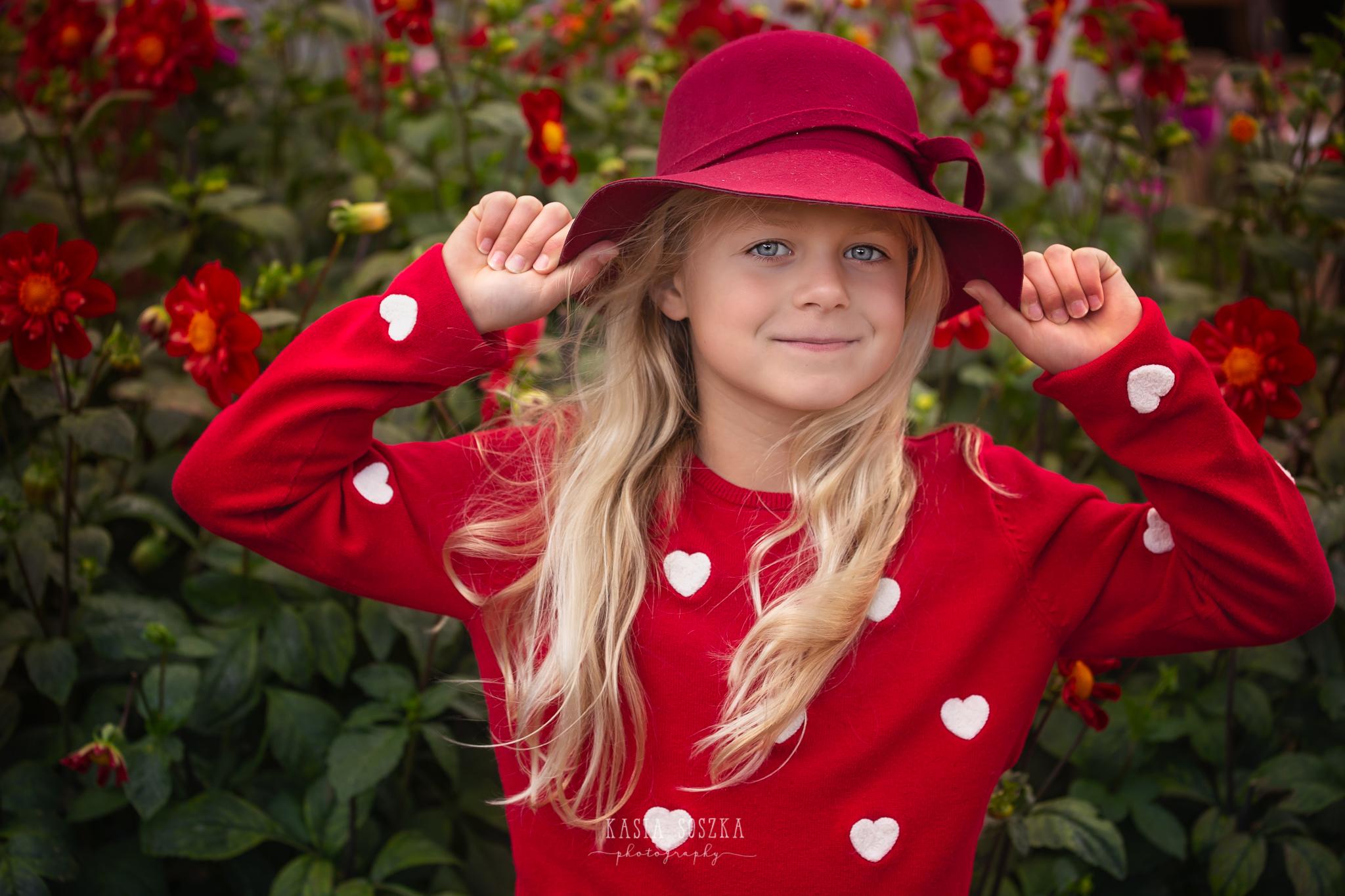 Children photography, child photographer Leeds, York, Bradford, Harrogate: pretty blond girl with blue eyes posing for a portrait against purple autumn flowers
