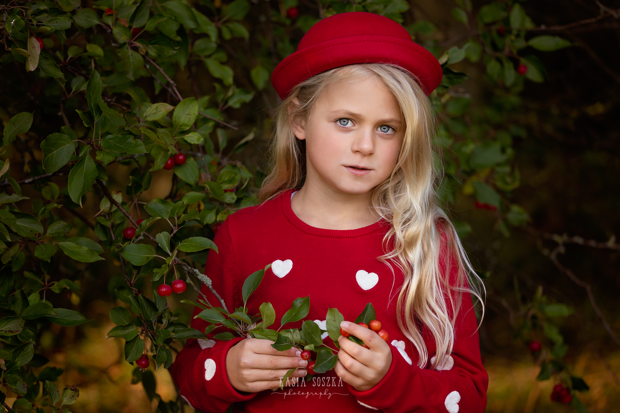 Child photography, child photographer Leeds, York, Bradford, Harrogate: pretty blond girl in red holding a berry tree branch