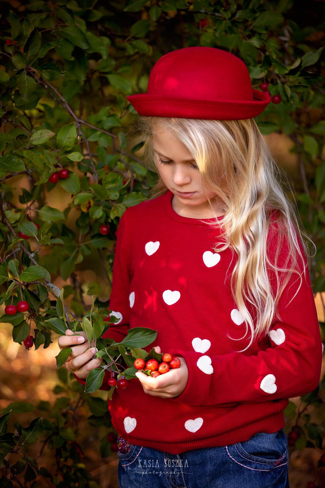 Children photography, child photographer Leeds, York, Harrogate, Bradford: beautiful blond girl in a red sweater holding a berry tree branch