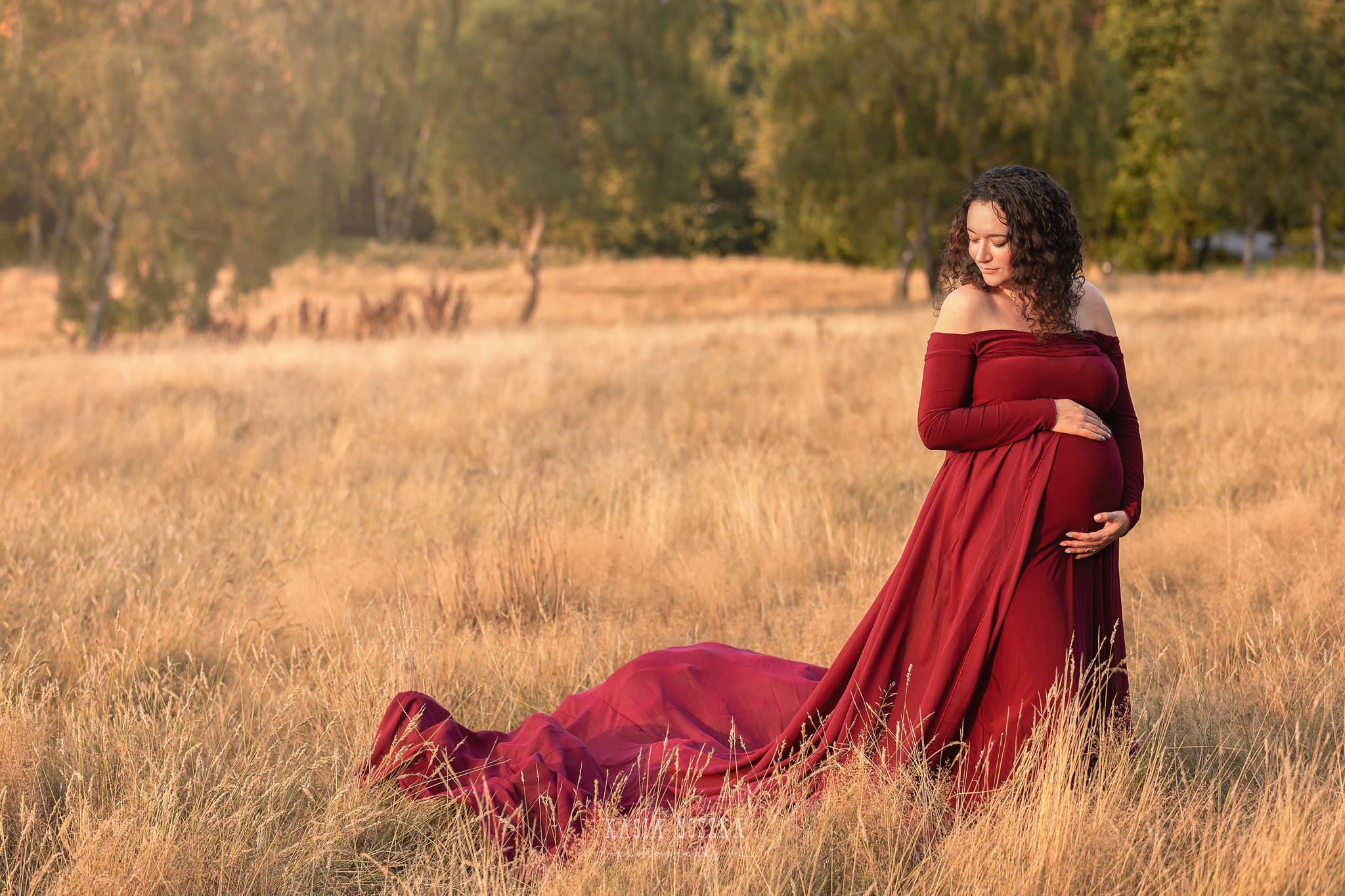 Maternity photography, maternity photographer Leeds , York, Harrogate, Bradford: woman in a long wine red dress posing for her pregnancy photos in a park in Leeds, Yorkshire, on a sunny autumn day