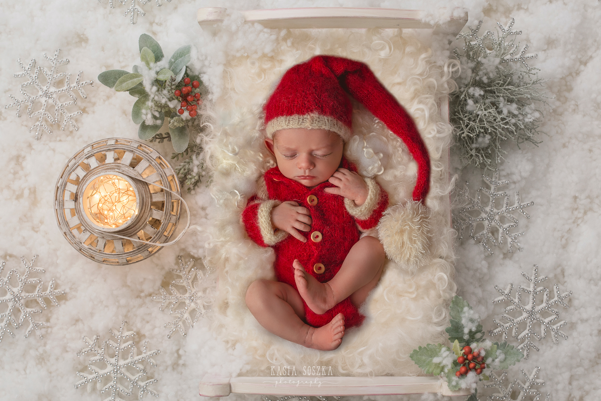 Newborn photography in Leeds near Bradford, York and Harrogate: cute newborn baby girl in Christmas outfit sleeping in a little bed