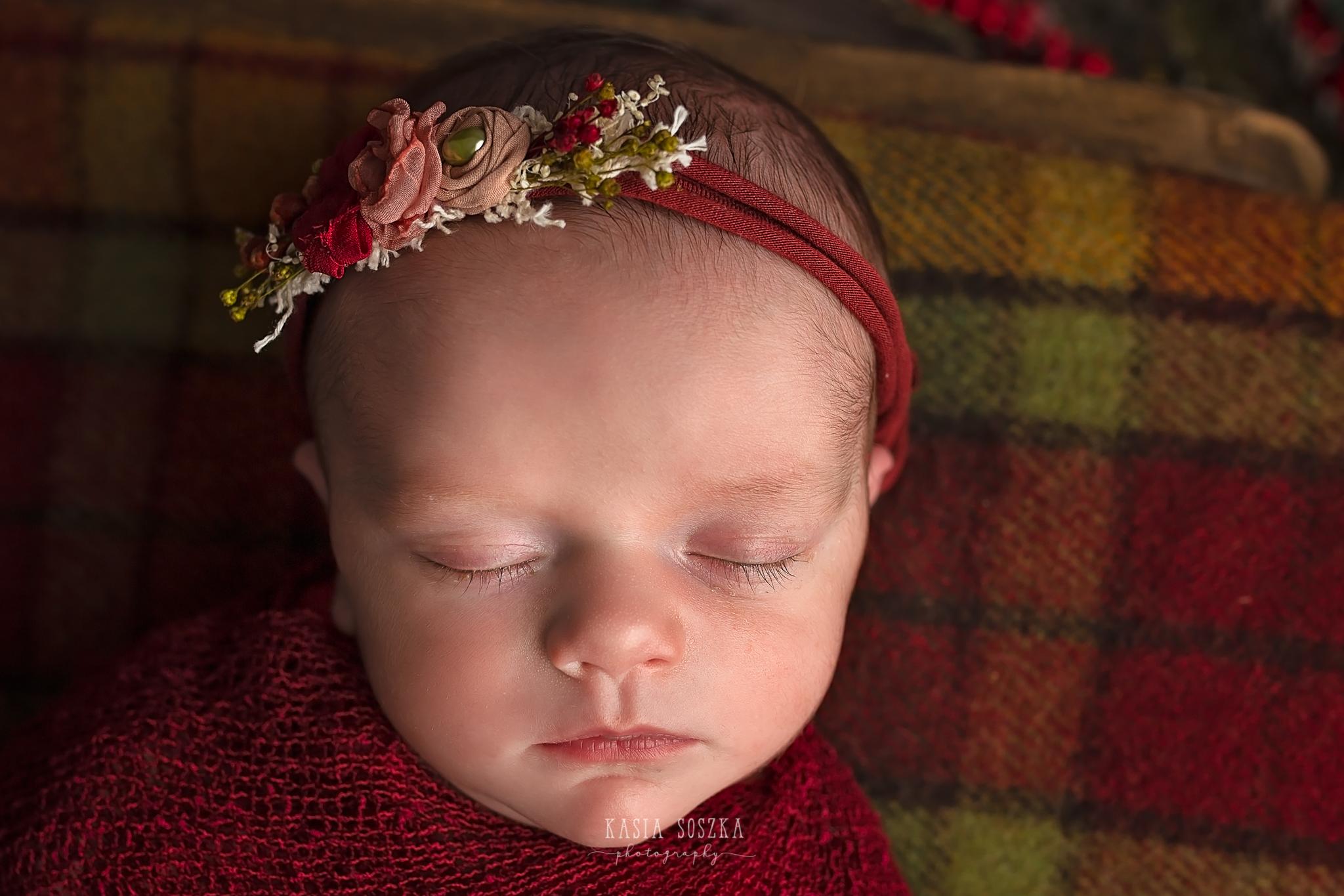 Newborn photography in Leeds near Bradford, York and Harrogate: close up of a cute newborn baby girl in Christmas set up