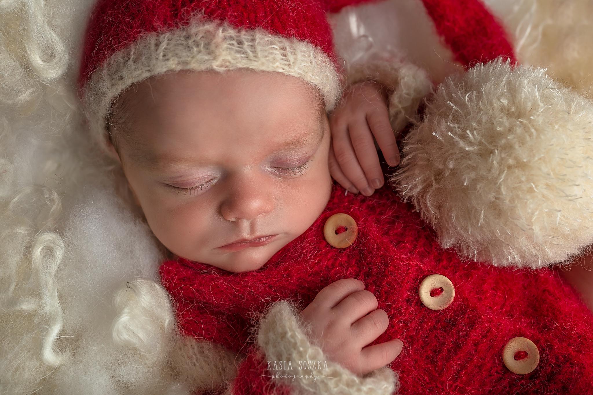 Newborn photography in Leeds near Bradford, York and Harrogate: cute newborn baby girl in Santa's outfit sleeping on a white fluffy blanket