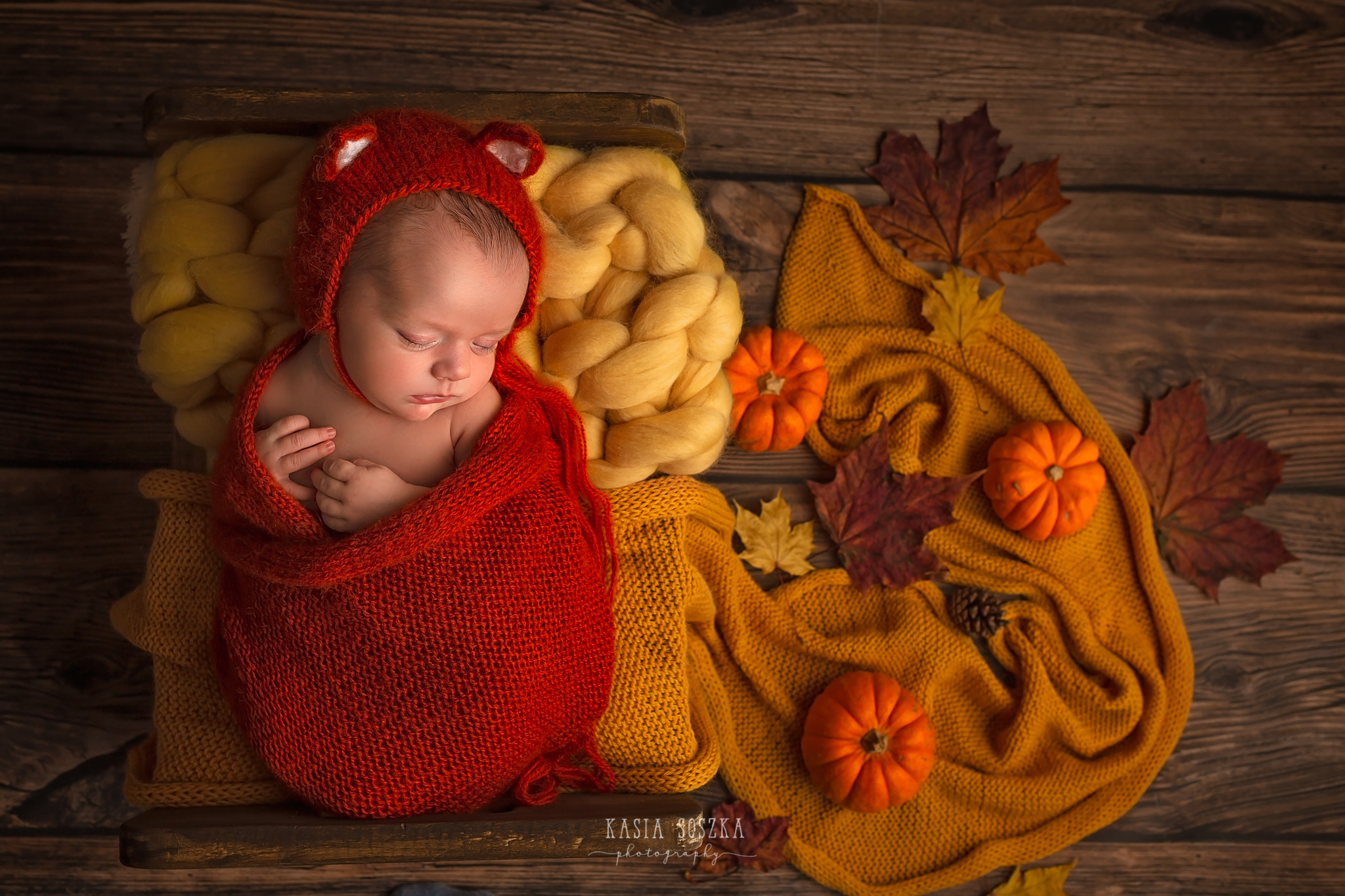 Newborn photography in Leeds near Bradford, York and Harrogate: cute newborn baby girl in fox outfit sleeping in a little bed