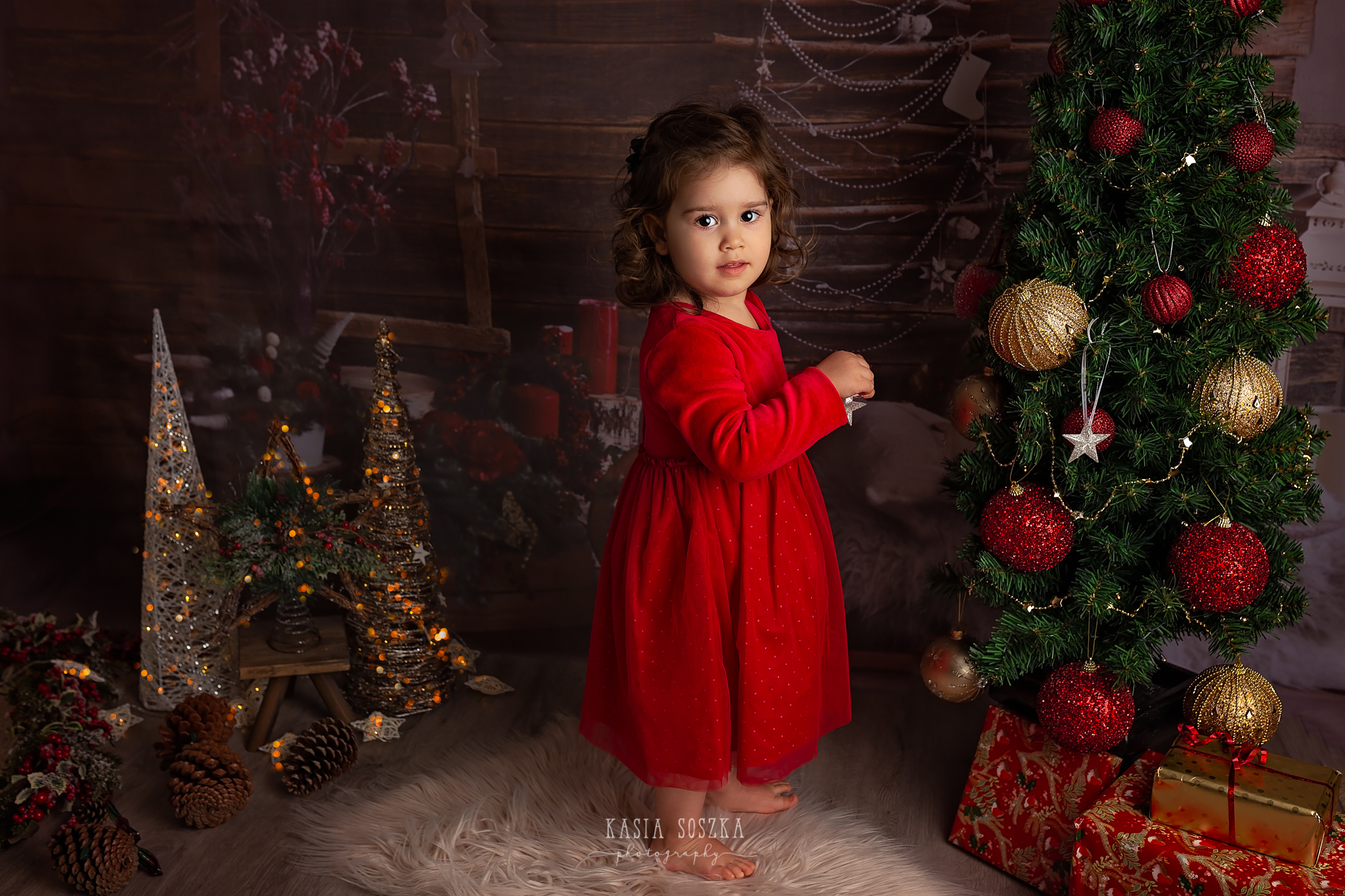 Child photographer Leeds, York, Bradford, Harrogate. Christmas Mini Sessions 2018 Leeds: beautiful little girl in a red dress decorating Christmas tree.