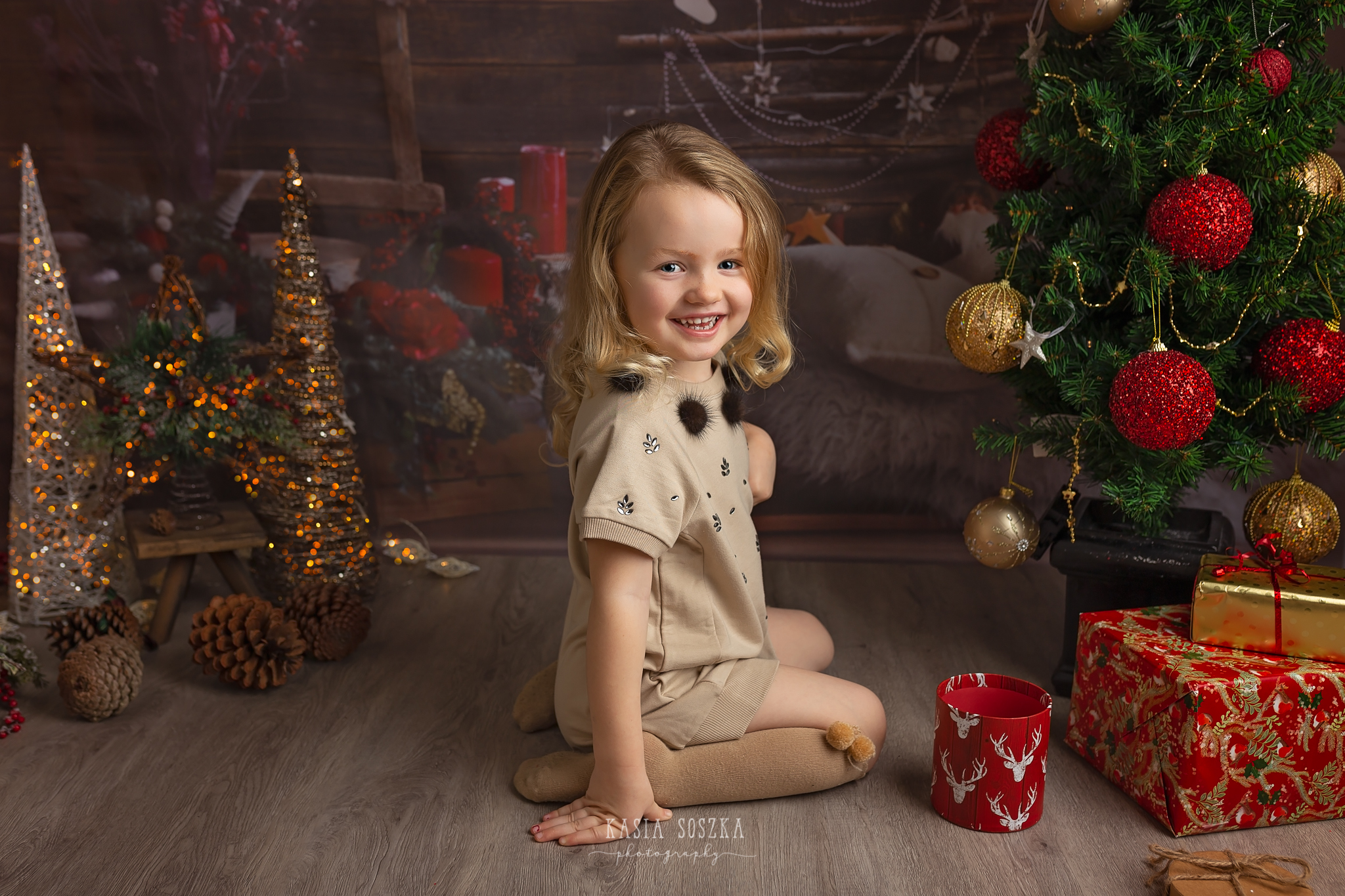 Child photographer Leeds, York, Bradford, Harrogate. Christmas Mini Sessions 2018 Leeds: beautiful little girl sitting by Christmas tree.