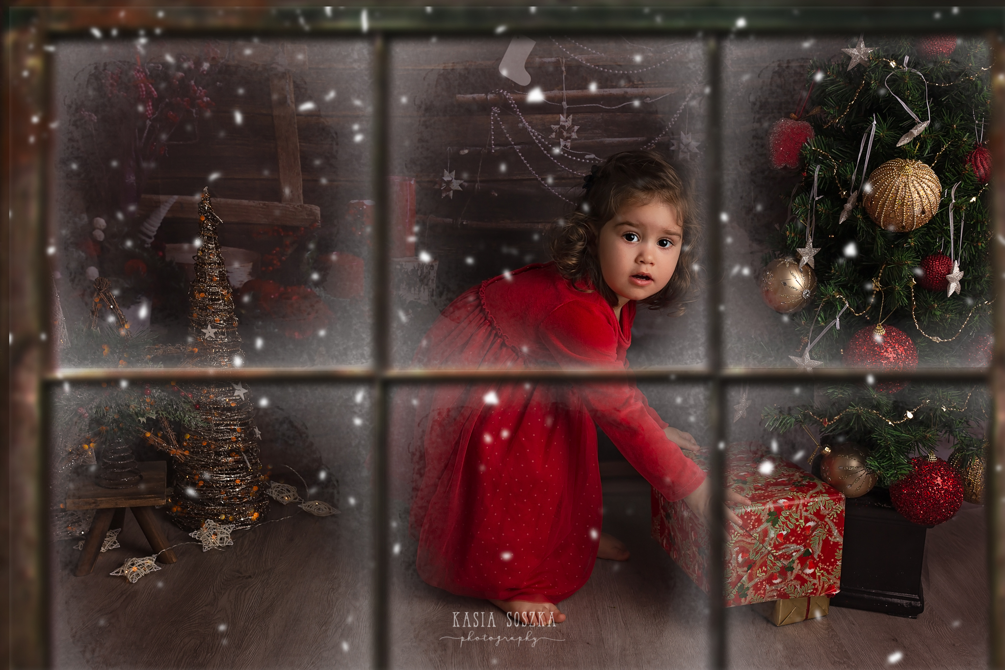 Child photographer Leeds, York, Bradford, Harrogate. Christmas Mini Sessions 2018 Leeds: beautiful little girl in a red dress checking presents under the Christmas tree.