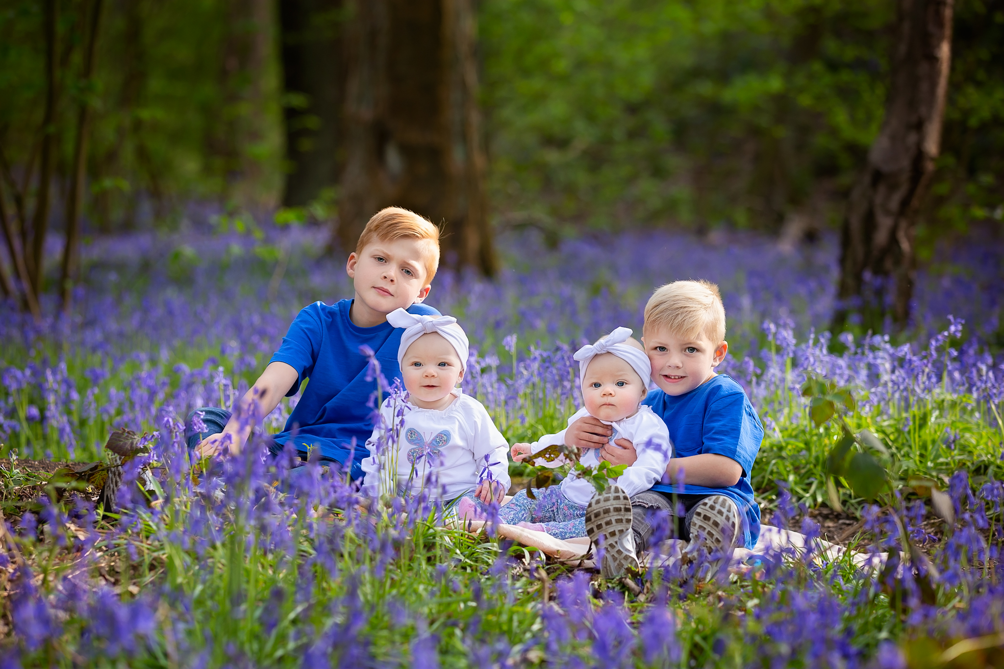 Children photographer Leeds, York, Harrogare, Bradford: twin baby girls with their older brothers during bluebell session in Leeds, West Yorkshire