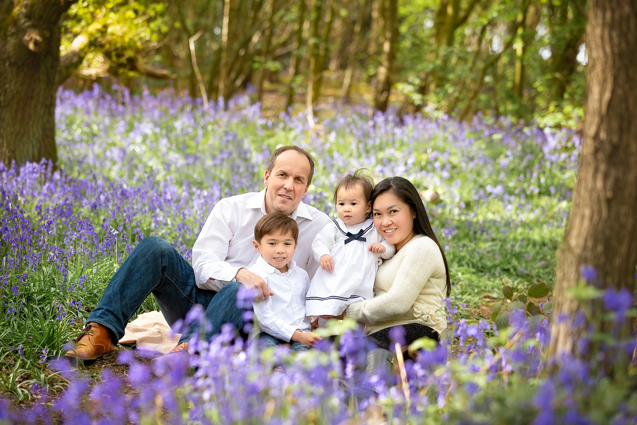 Family photography Leeds, York, Harrogare, Bradford: family of 4 posing for a family picture in a bluebell wood in Leeds, Yorkshire