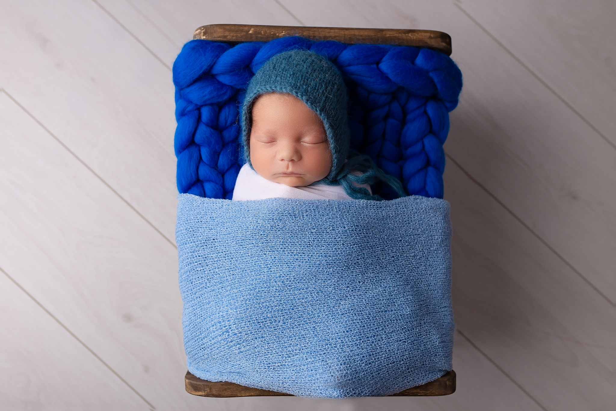 Newborn photographer Leeds, York, Bradford, Harrogate, Wakefield: newborn baby boy sleeping in a tiny bed during his newborn photoshoot in Leeds