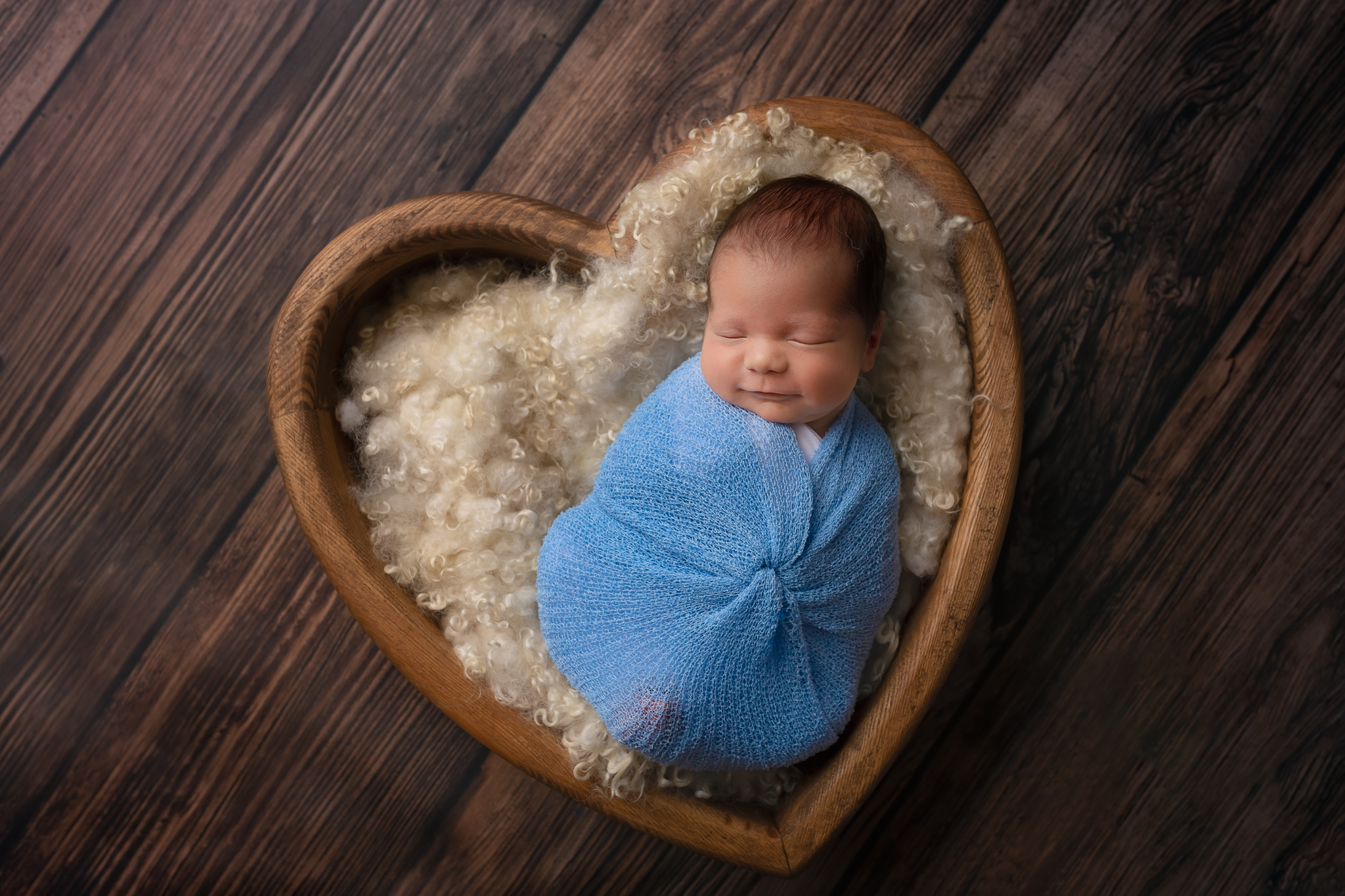 Newborn photographer Leeds, York, Bradford, Harrogate, Wakefield: newborn baby sleeping in a heart shaped bowl during his newborn photoshoot in Leeds, West Yorkshire