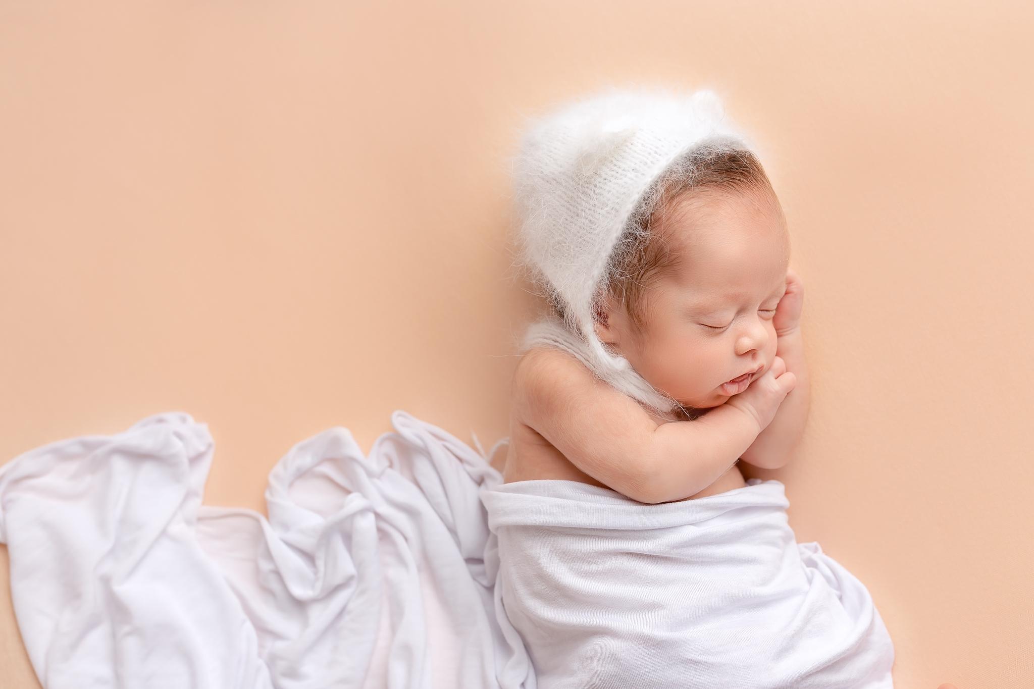 Professional newborn photography Leeds-York-Bradford-Harrogate-Wakefield: newborn baby girl sleeping on a peach blanket during her newborn photoshoot in Leeds, Yorkshire