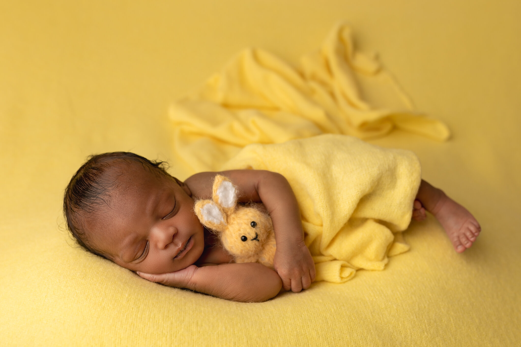 Professional newborn photography Leeds, York, Bradford, Wakefield, Harrogate, Huddersfield: baby boy sleeping on a yellow blanket during newborn session in Leeds, West Yorkshire