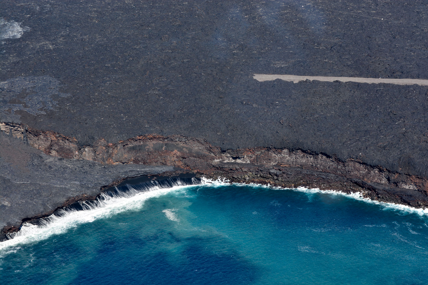 A close-up of the lava entering the ocean as well as a road that was blocked off by active lava flow