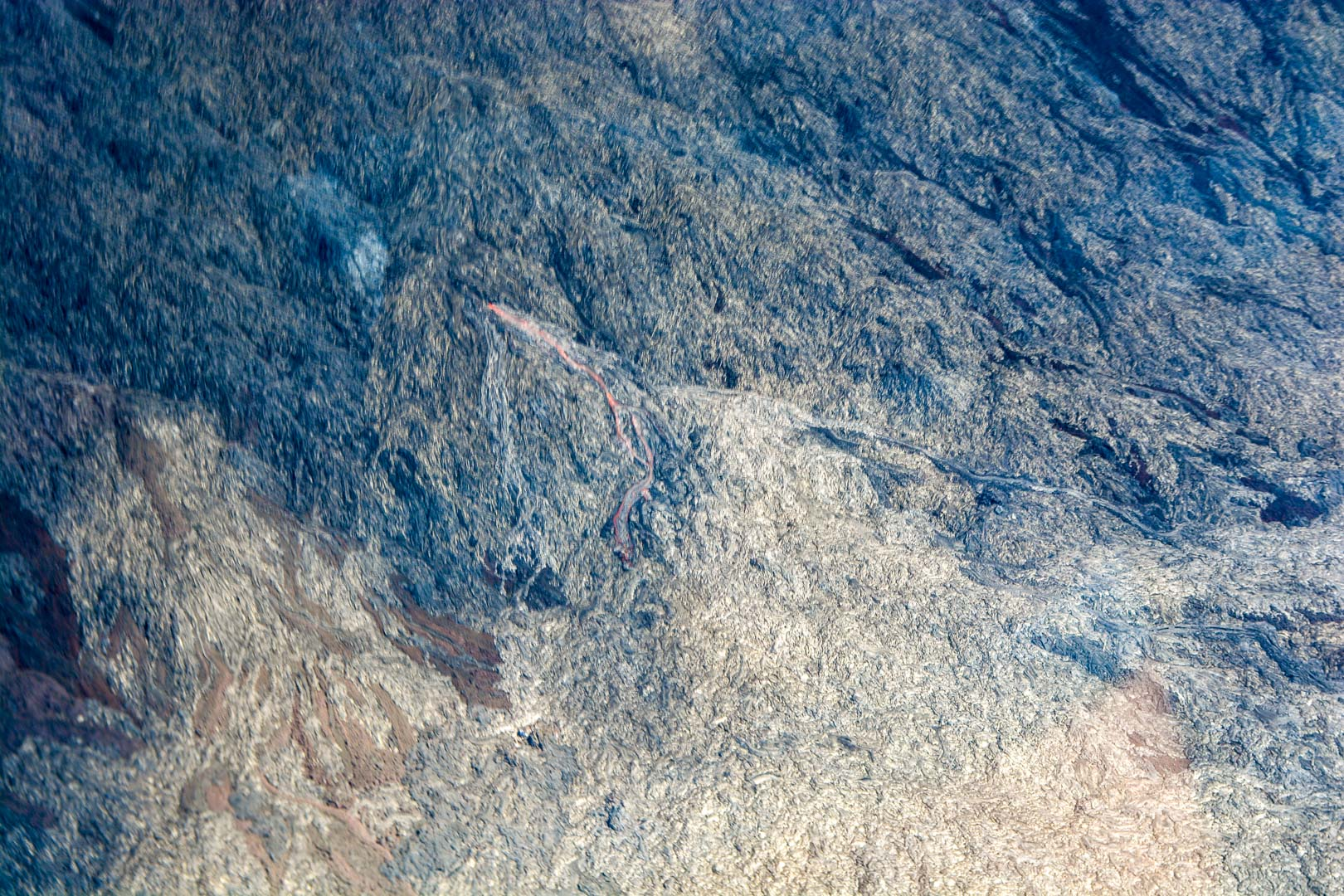 See if you can spot the lava flow. In daylight, lava looks black, making it undetectable from older cooled-off lava. The orange color we're used to seeing is more prevalent at night.