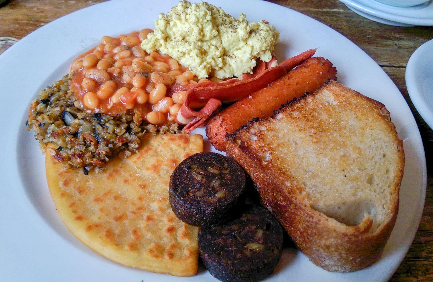 A small vegan Scottish Breakfast: veg. haggis, baked beans, scrambled tofu, veg. bacon, veg. sausage, toast, veg. black pudding, and a tattie scone!