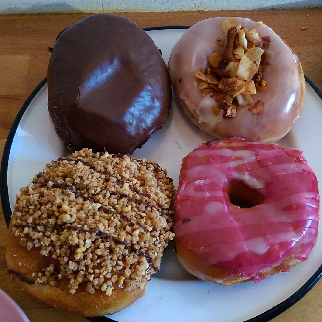 Starting from the top left and going clockwise: Boston Cream, Maple frosted with Coconut Bacon, Nutella filled, and Raspberry frosted—all of this delciousness is vegan!