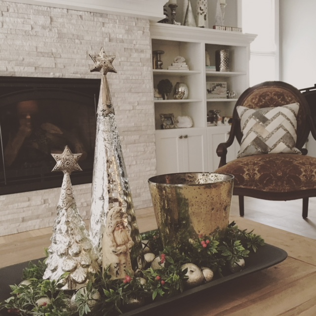 Trees, Santa, silver bells in tray, and large mercury glass candle from HomeGoods. On shelves in background, mercury vases, geodes and pillow on chair from HomeGoods