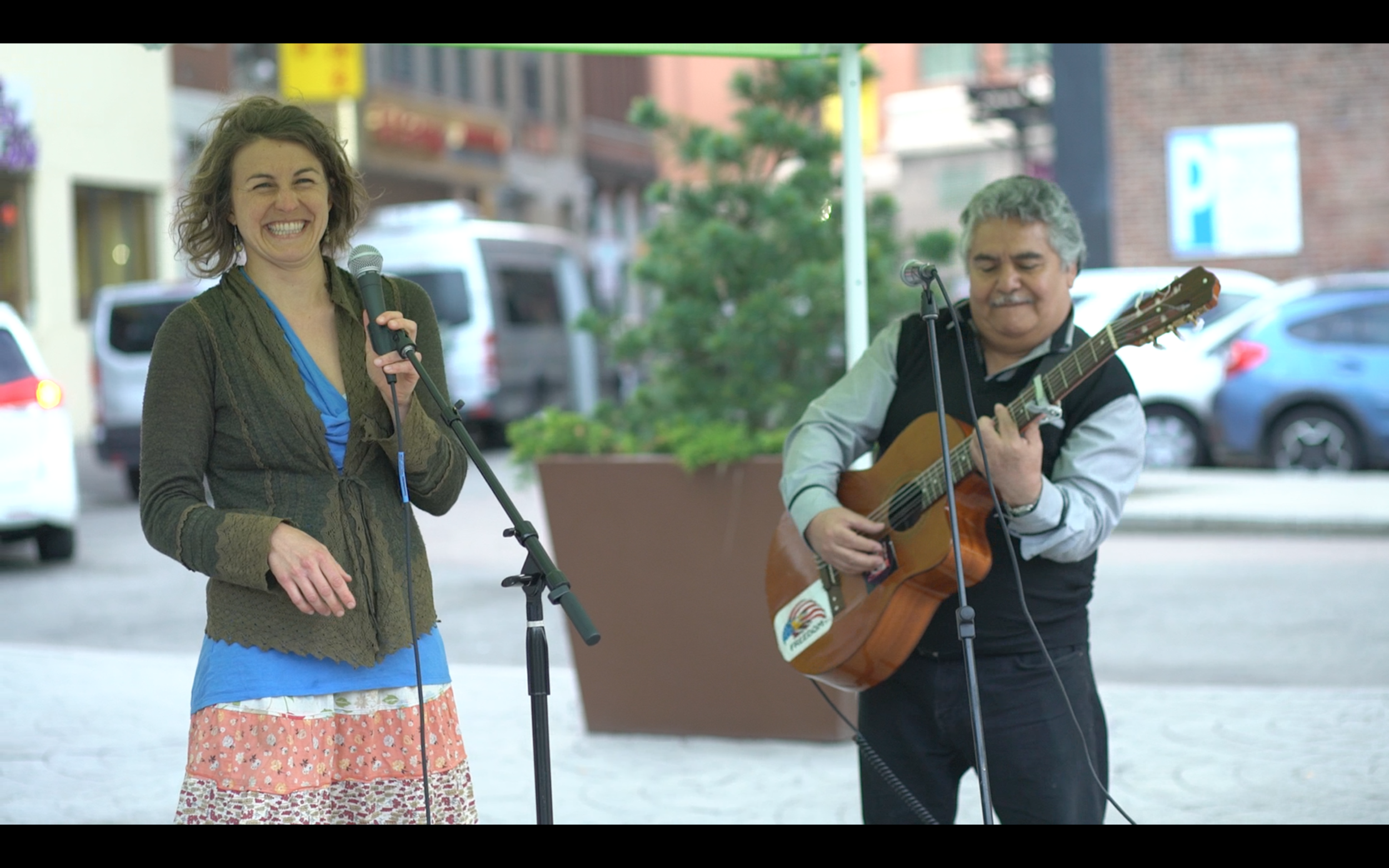 Julie Kurtz, graduate student at Tufts, shares an impromptu song with Cesar del Cid (of Guatemala and Boston) at the International Song Exchange, Chinatown Gate/Rose Kennedy Greenway park.