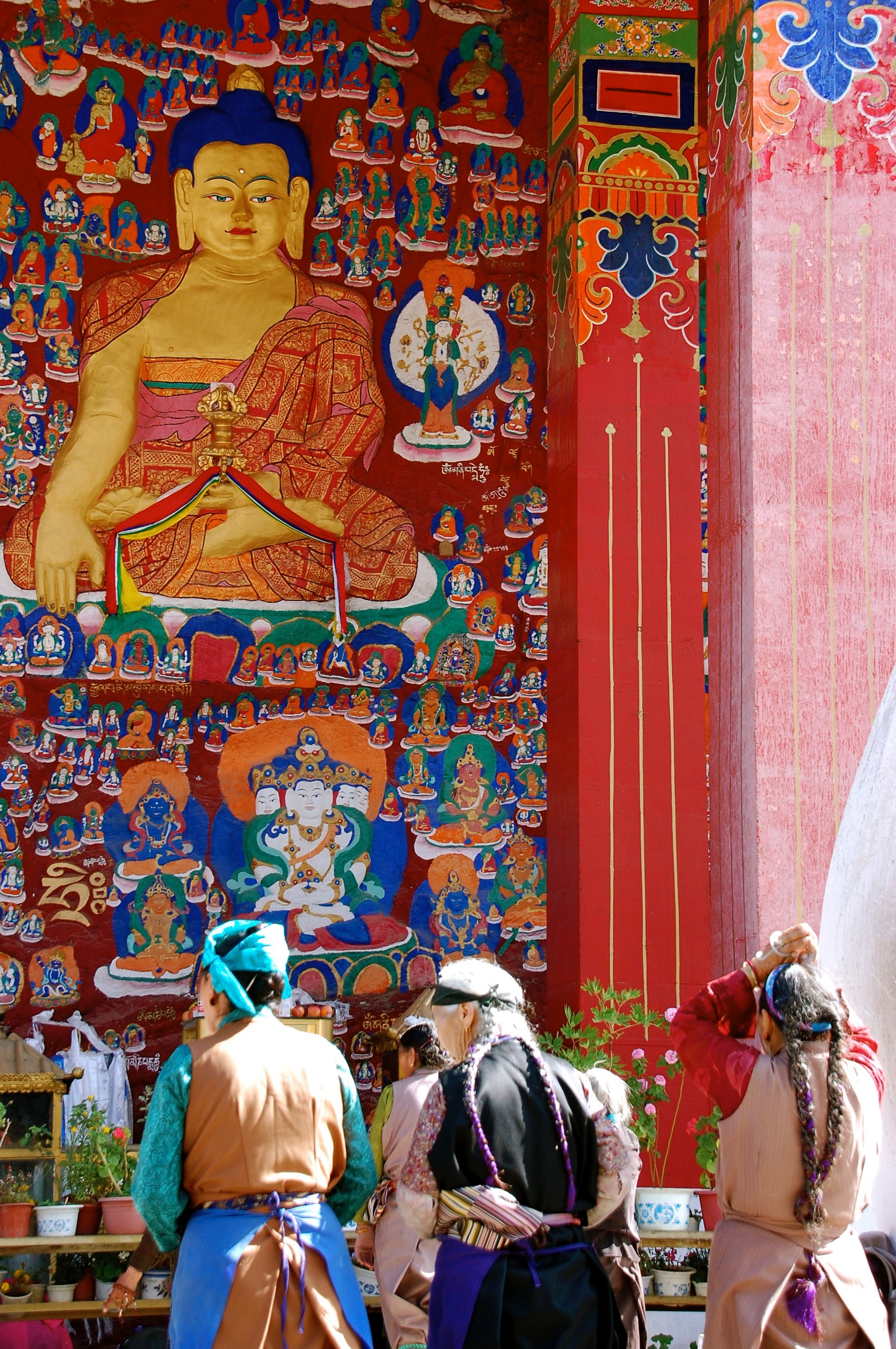 Devotees make prostrations at the 10,000 Buddha Wall, where in past times bodies of the deceased whose families could not afford a proper burial would be left for the monks to perform last rites (Lhasa, Tibet)