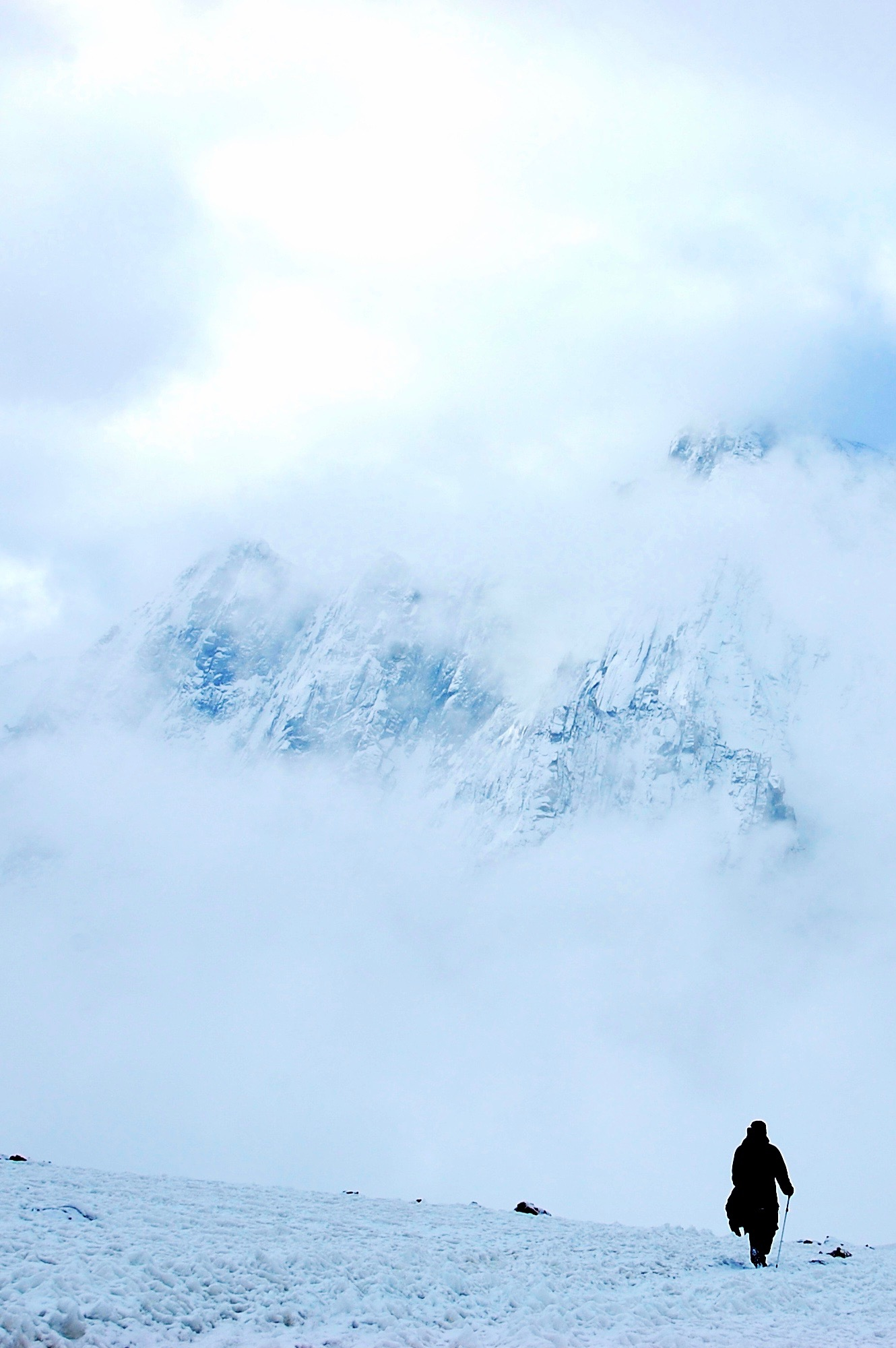 A pilgrim descends through the clouds from 19,500ft Dolma-la Pass, highest point of the parikrama (Mount Kailash, Tibet)