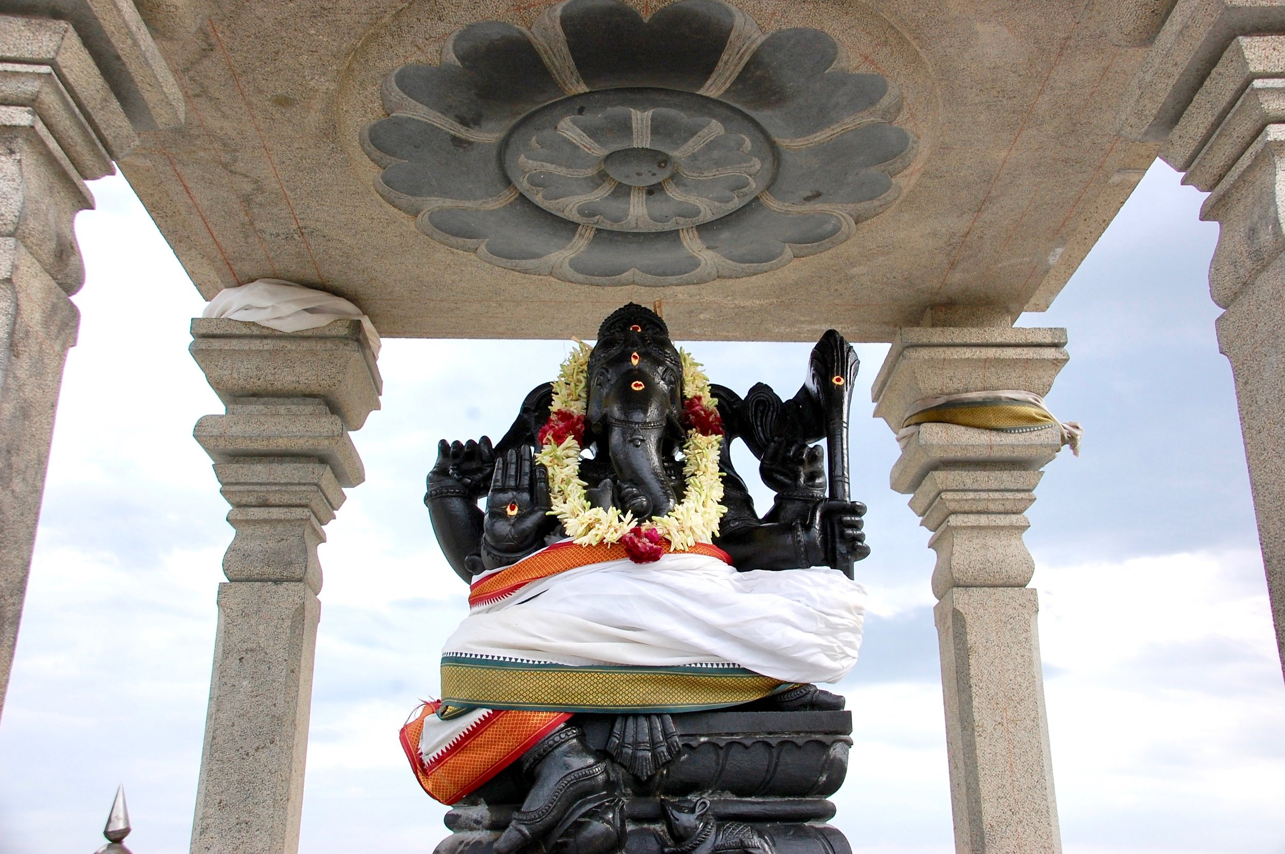 Ganesha, placed here at the highest point of the temple against a backdrop of sky, symbolizes the complete awakening of kundalini from Muladhara to Svadishthana (Olilayam, Tamil Nadu)